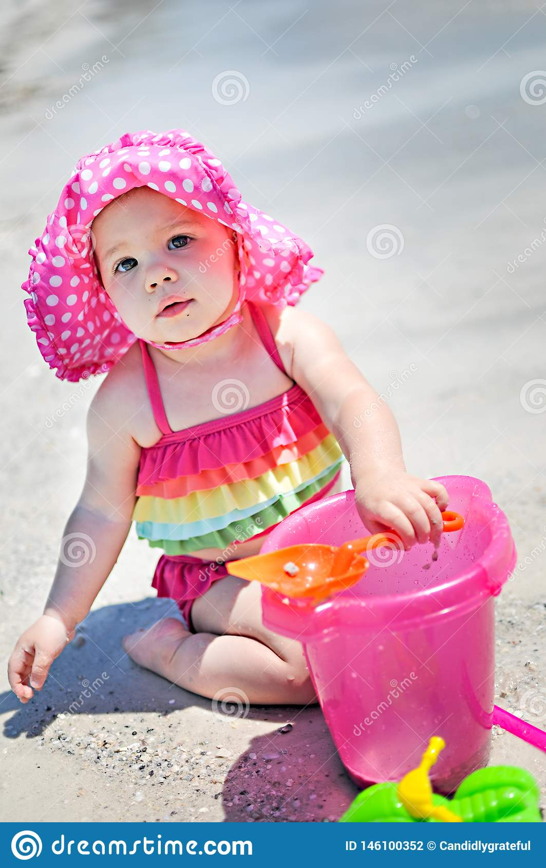 Ребенок со шляпой солнца на игре в песке на пляже