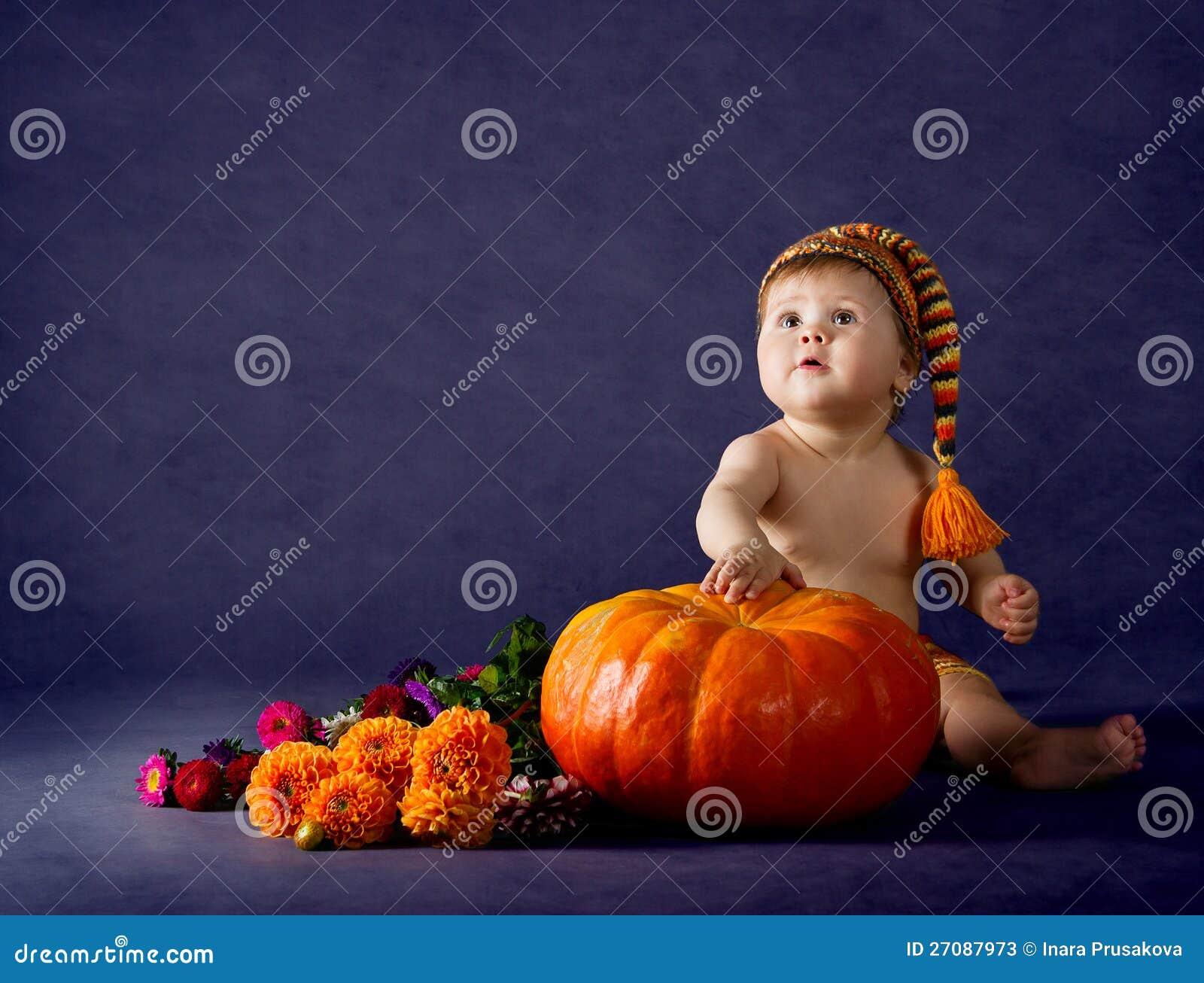 Ребенок с большой тыквой над пурпуровой предпосылкой.