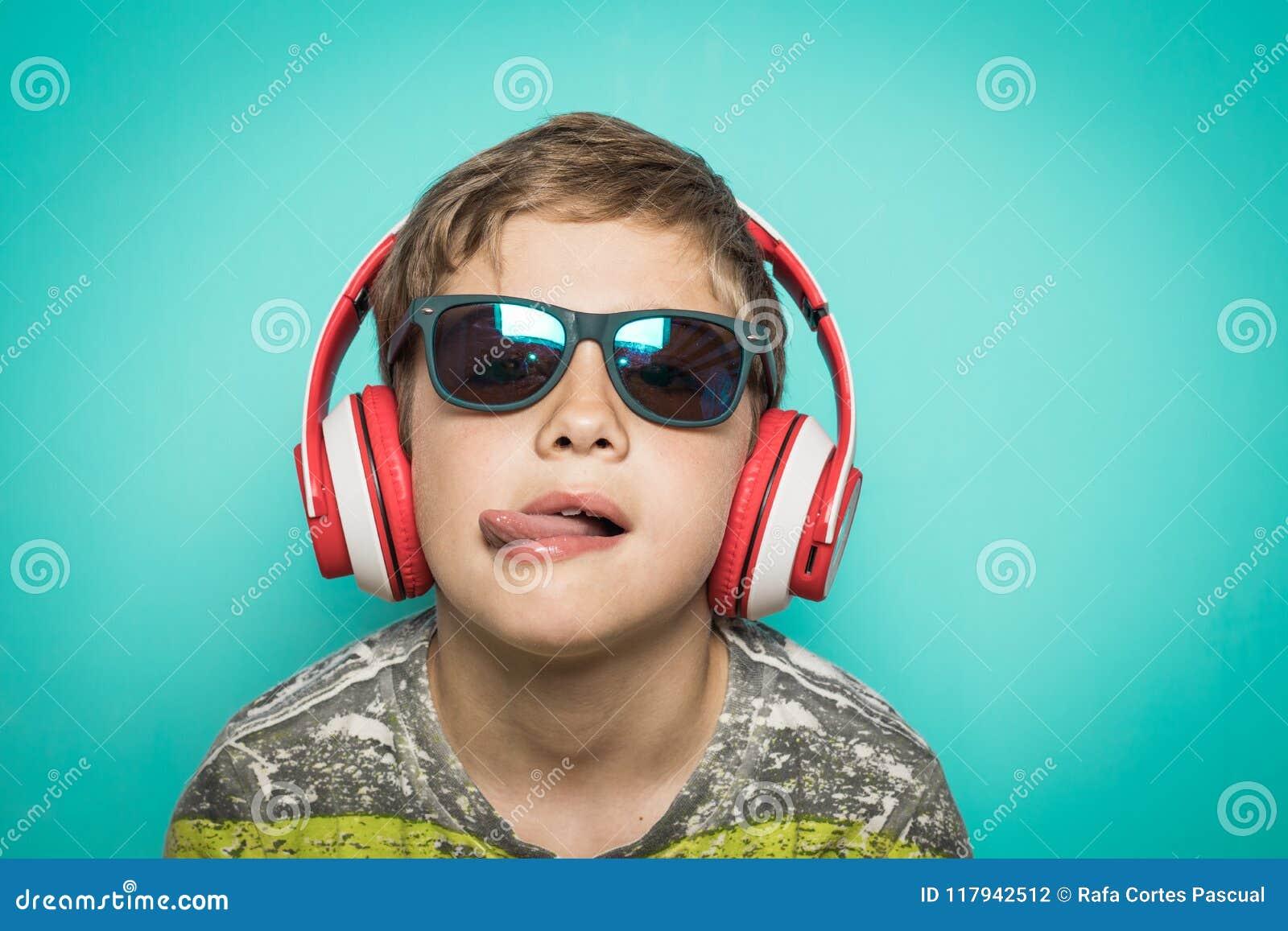 Ребенок с наушниками музыки и смешного выражения