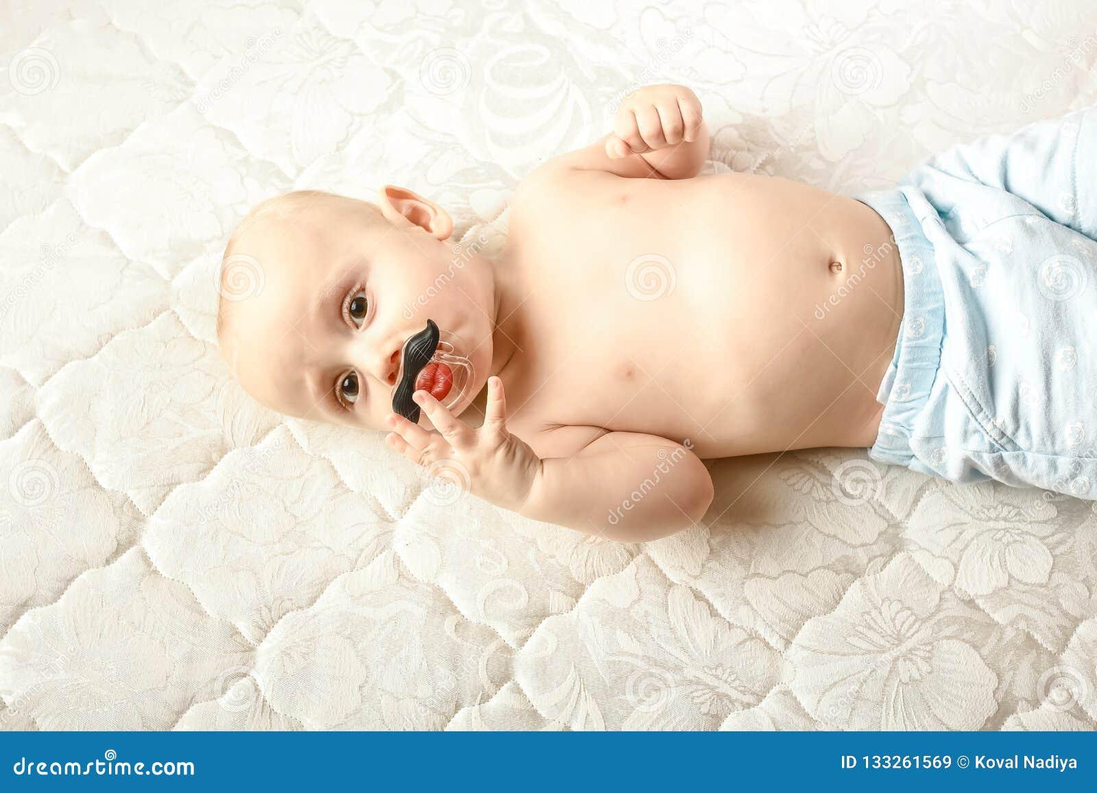 Ребенок с pacifier смешным с усиком и губами Ребенок в связанной крышке
