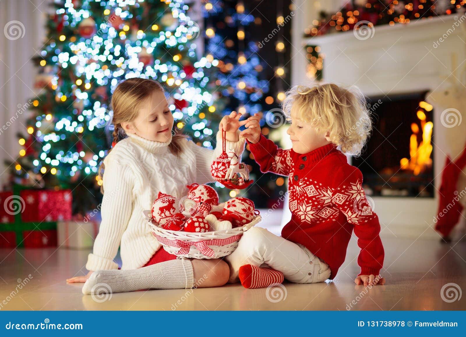 Ребенок украшая рождественскую елку дома Мальчик и девушка в связанном свитере с handmade орнаментом Xmas Праздновать семьи