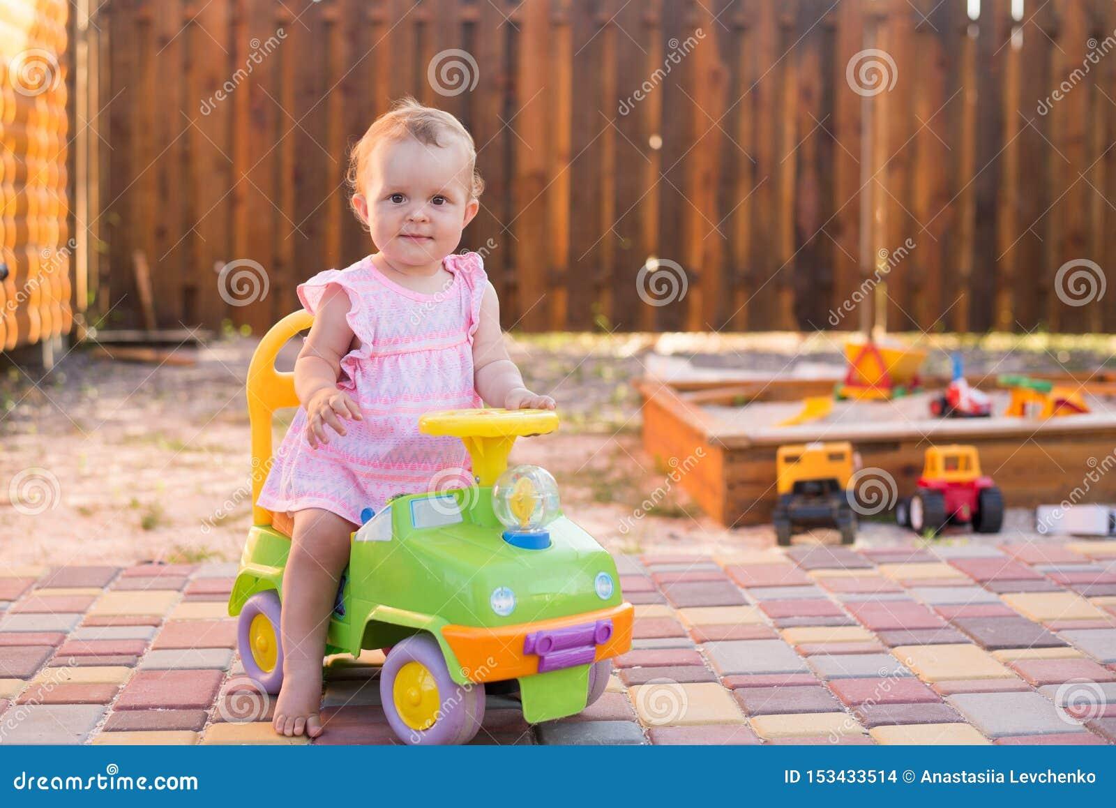 Ребенок управляя автомобилем игрушки на спортивной площадке на открытом воздухе, предпосылке лета, космосе экземпляра