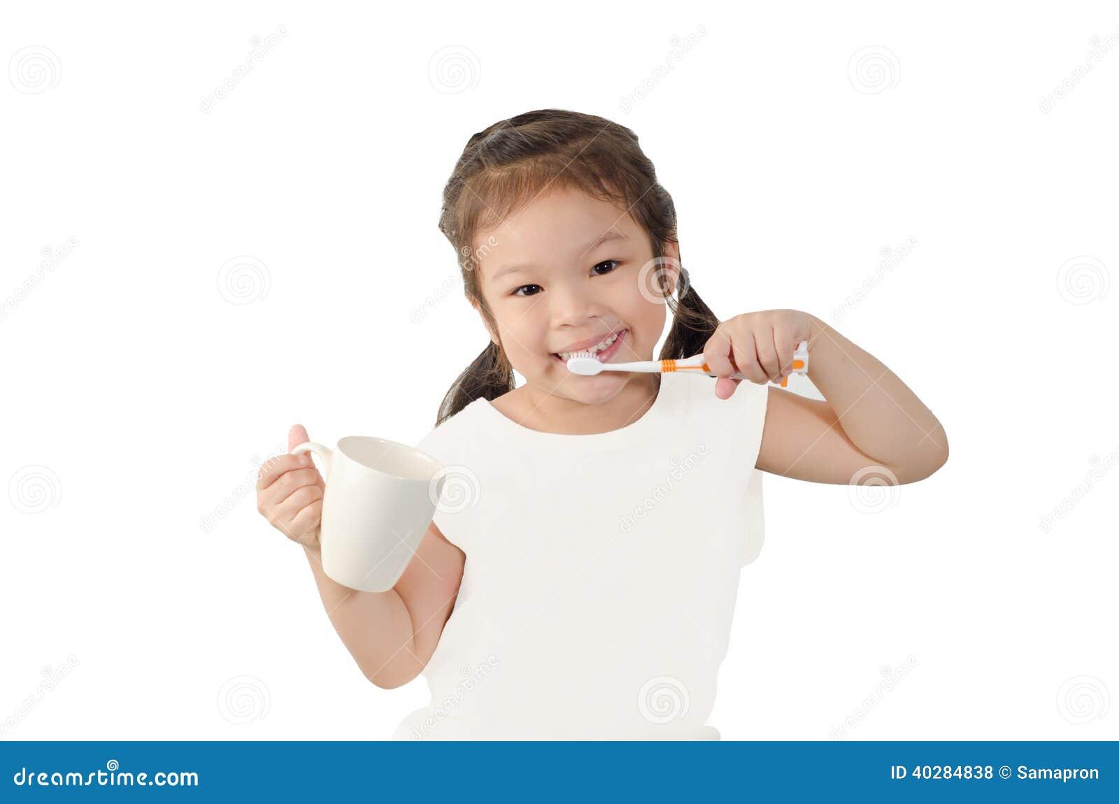 Ребенок чистя ее зубы щеткой