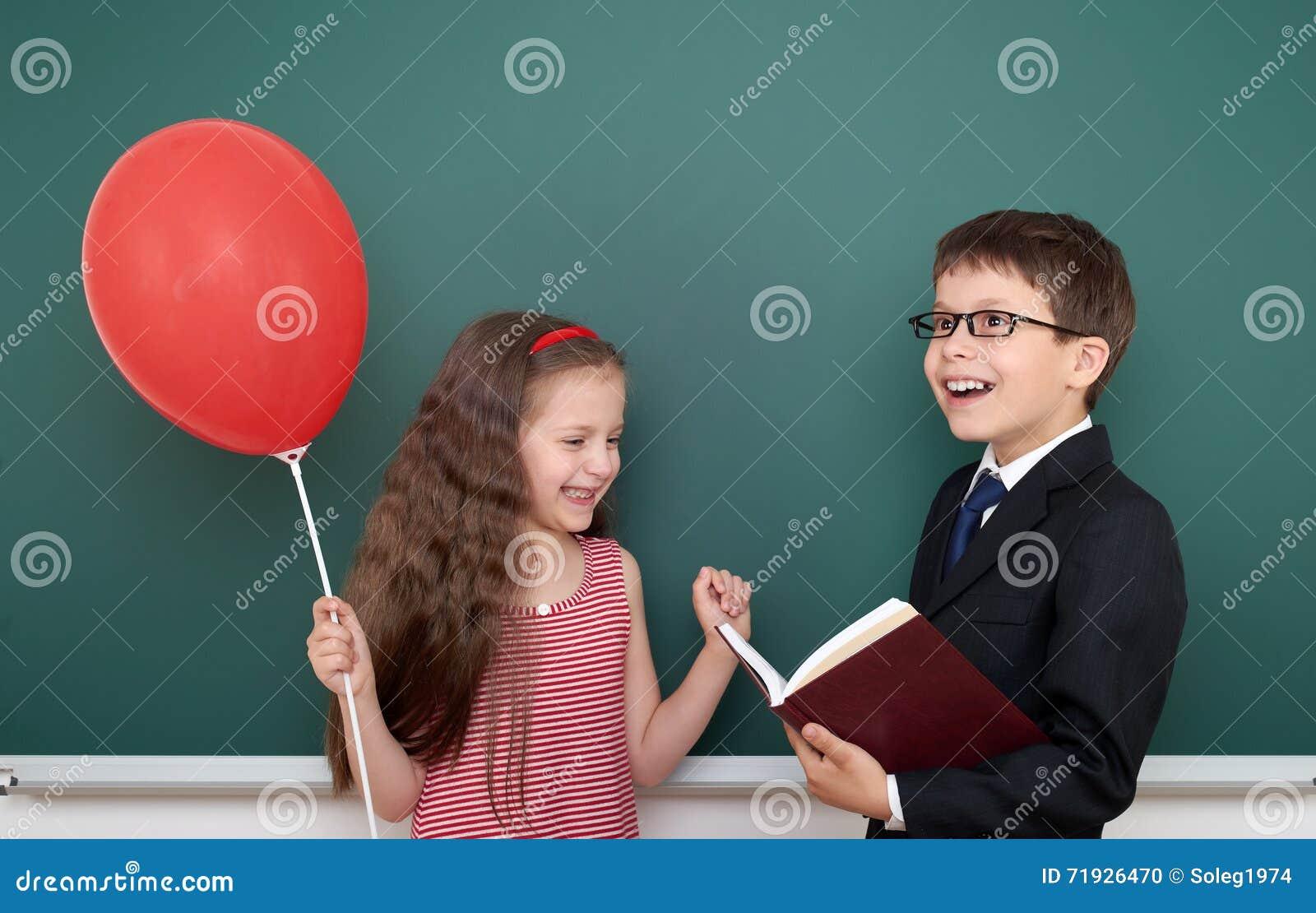 Ребенок школьника и девушки с воздушным шаром на предпосылке доски имея потеху