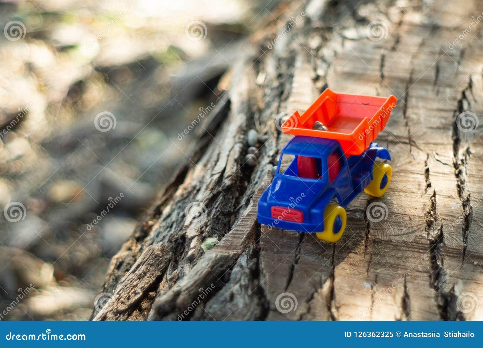 ребенок outdoors играя Ребенк мы льем песок в красную тележку Мальчик игр a улицы детей играя с машиной на большом журнале