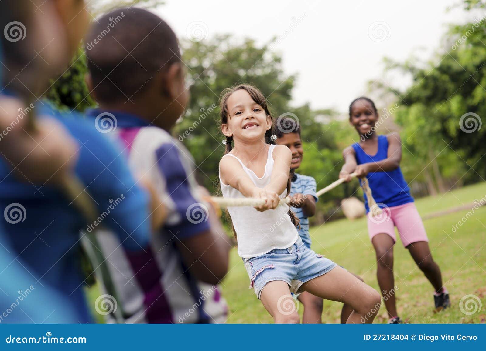 Ребеята школьного возраста играя перетягивание каната с веревочкой