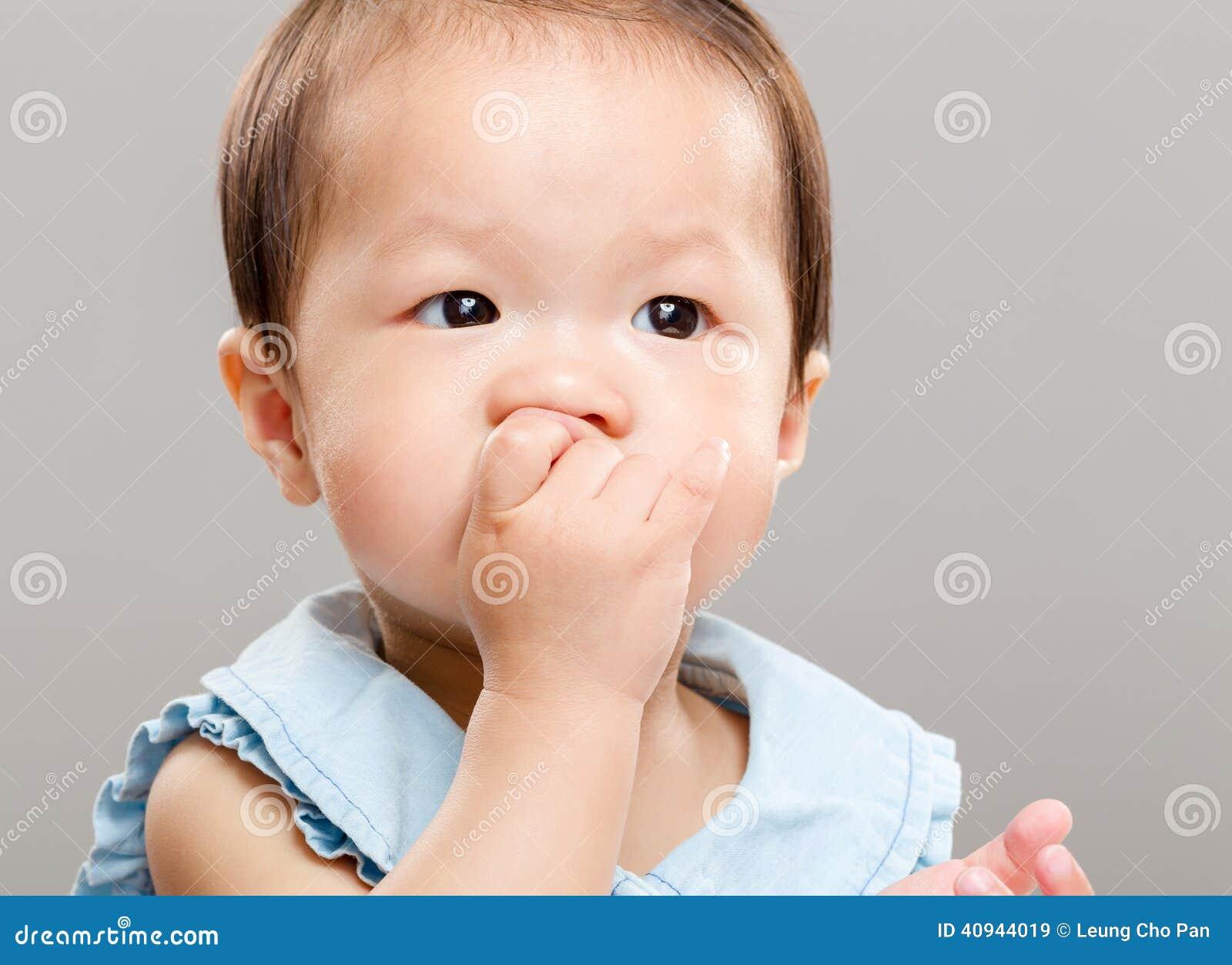 Ребёнок всасывая ее палец в рот