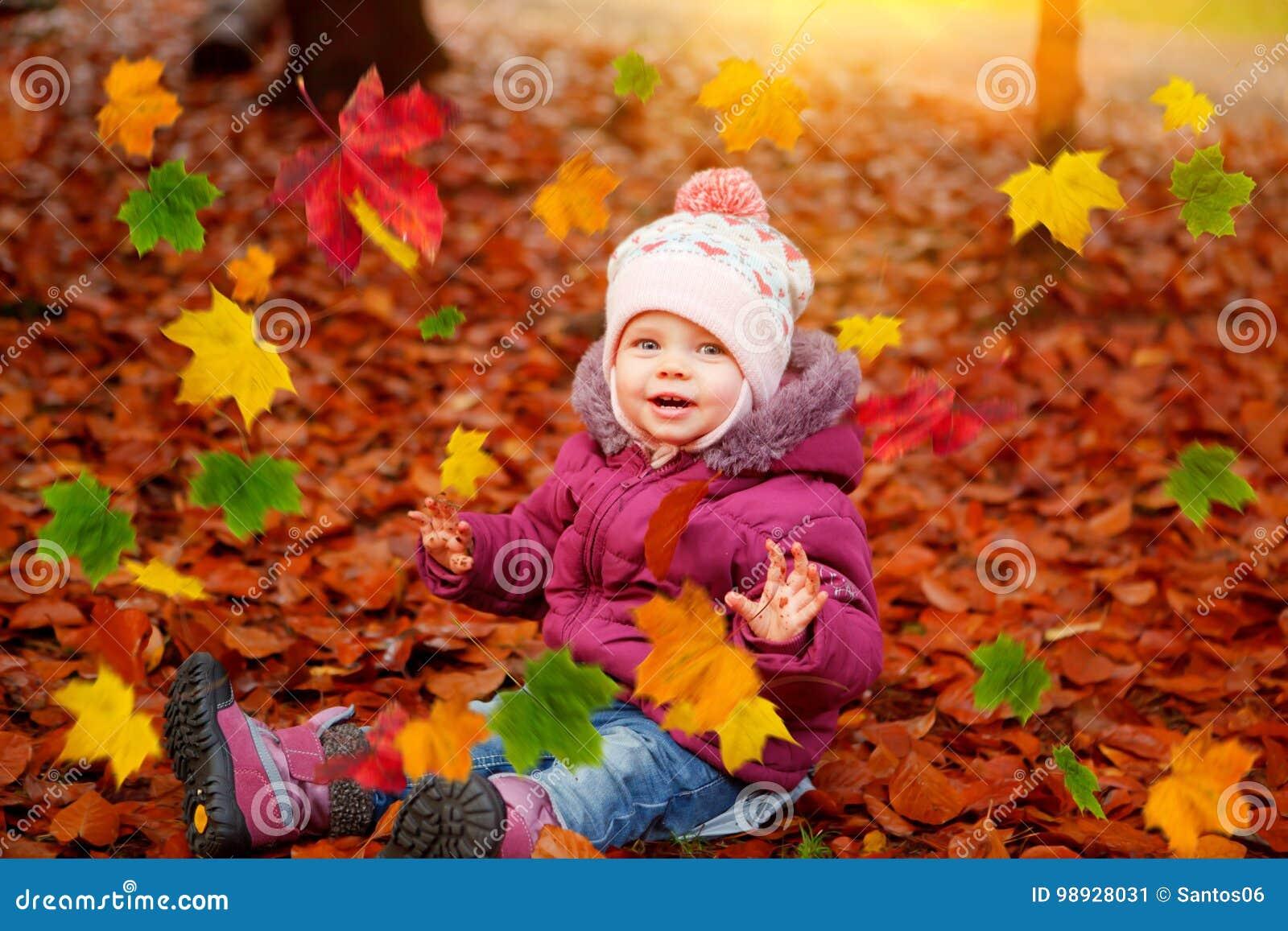Ребёнок играя с листьями осени