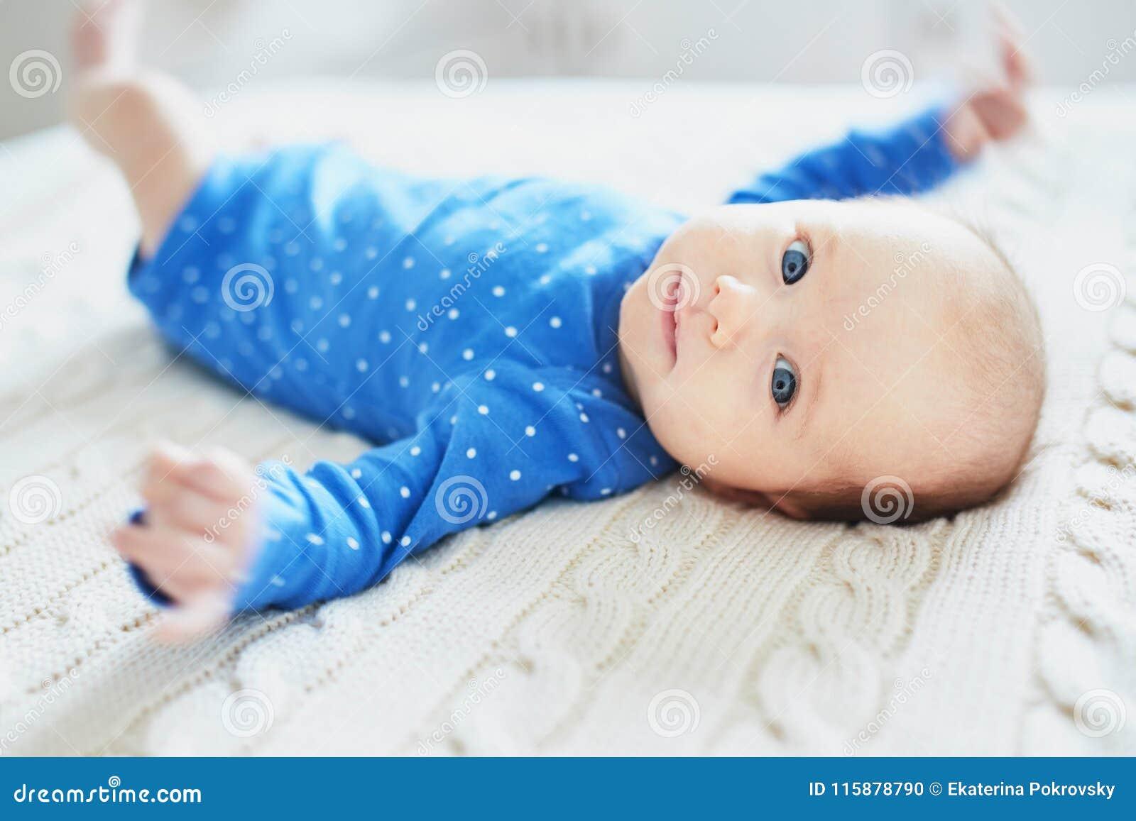 Ребёнок нося голубые одежды ослабляя в спальне