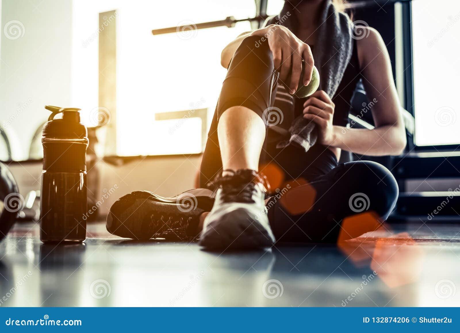 Резвитесь женщина сидя и отдыхая после разминки или тренировки в пригонке