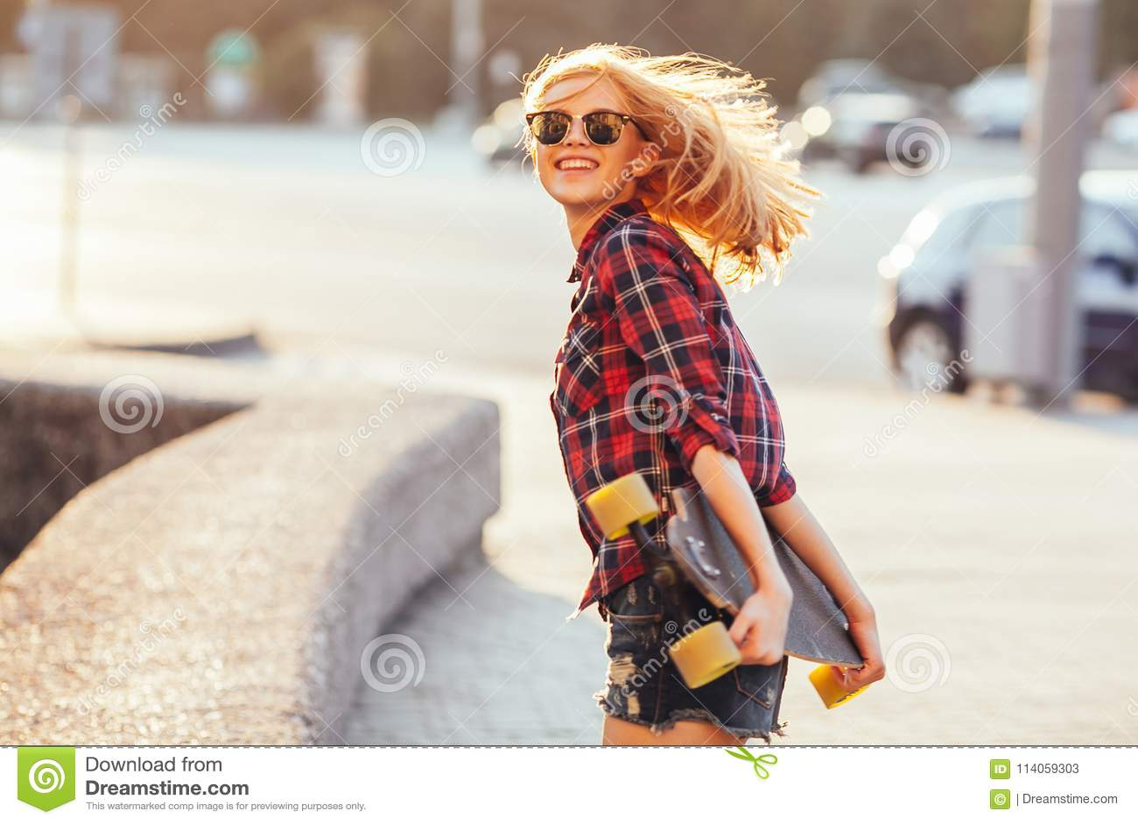 Резвитесь счастливая девушка представляя в лете с скейтбордом Стильная удачливая женщина битника с красочным longboard в заходе с