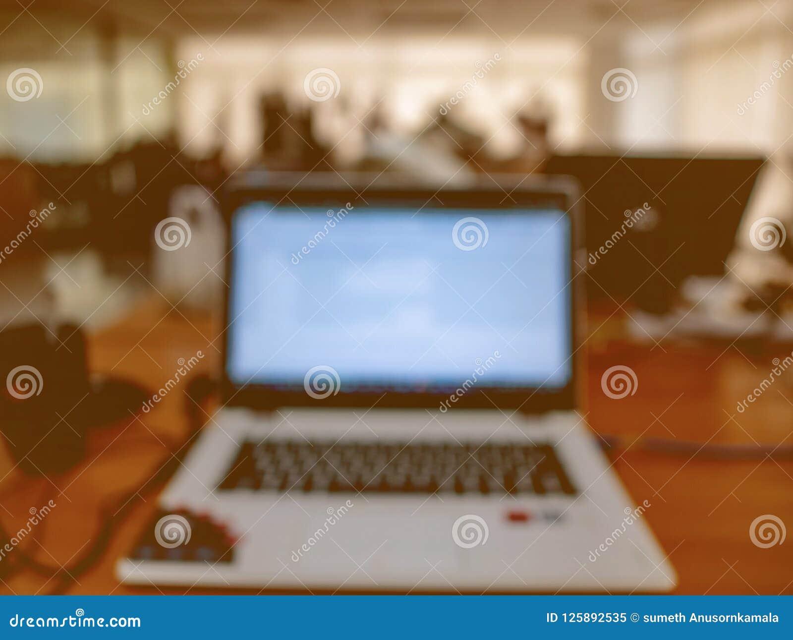 Резюмируйте запачканное фото компьтер-книжки в офисе