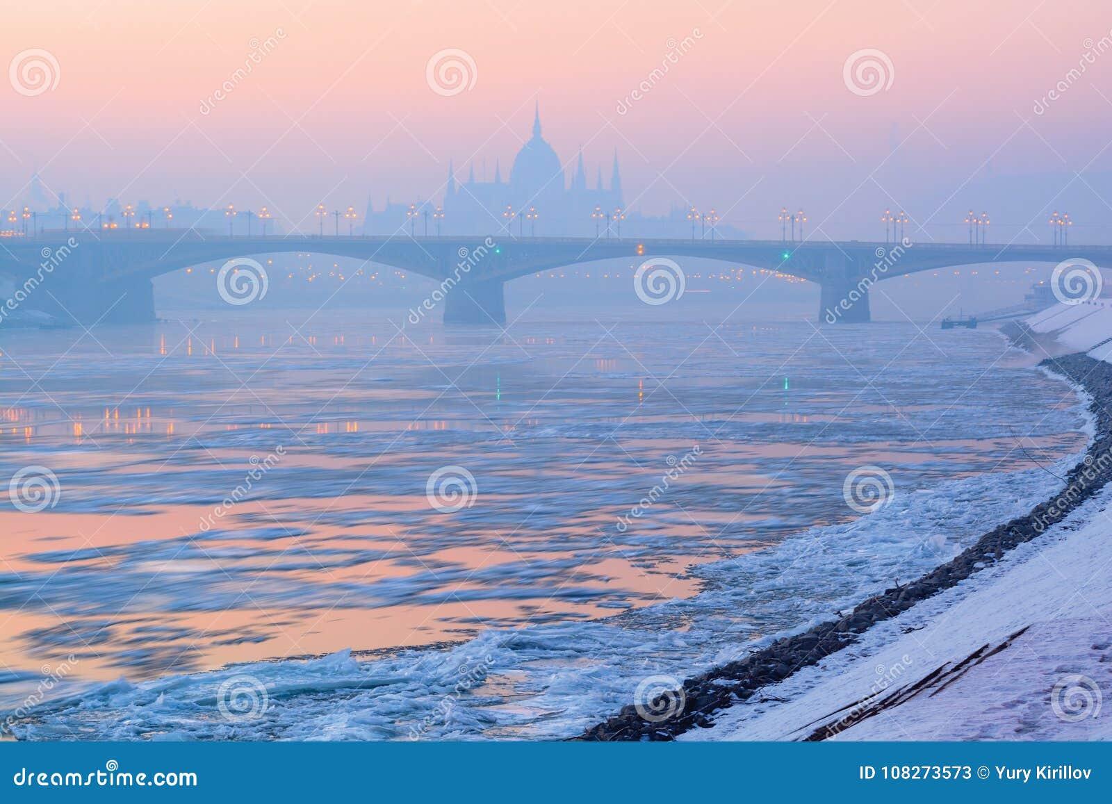 Река, дрейфующие льды, мост Маргарета, парламент конспектирует в зиме, Будапеште