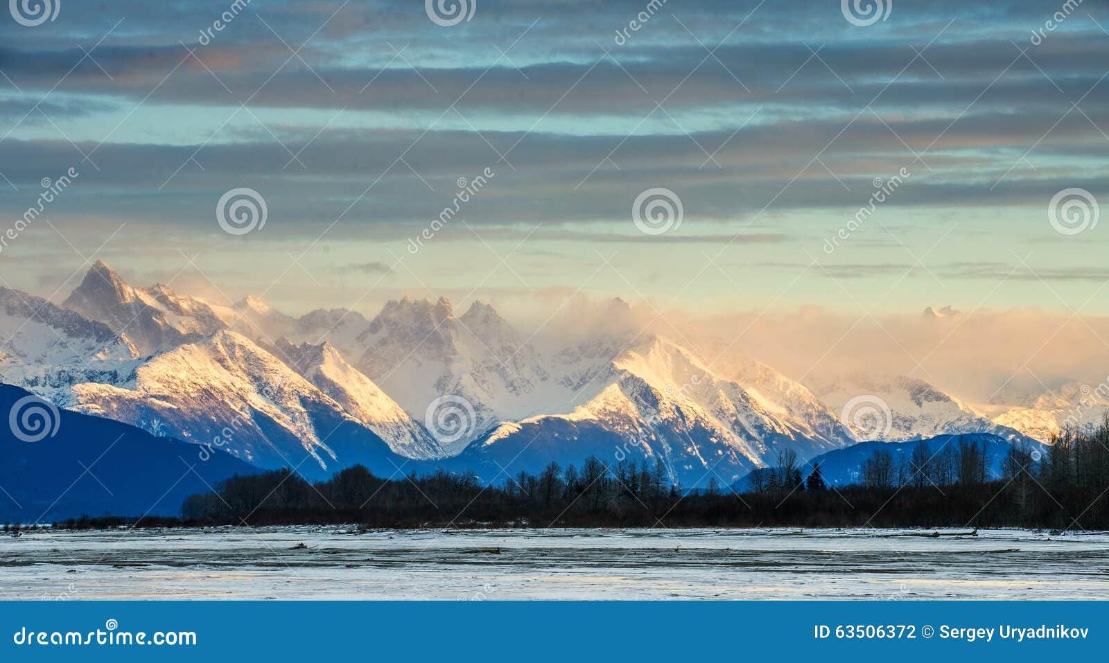 Река и горы Chilkat в снеге на восходе солнца