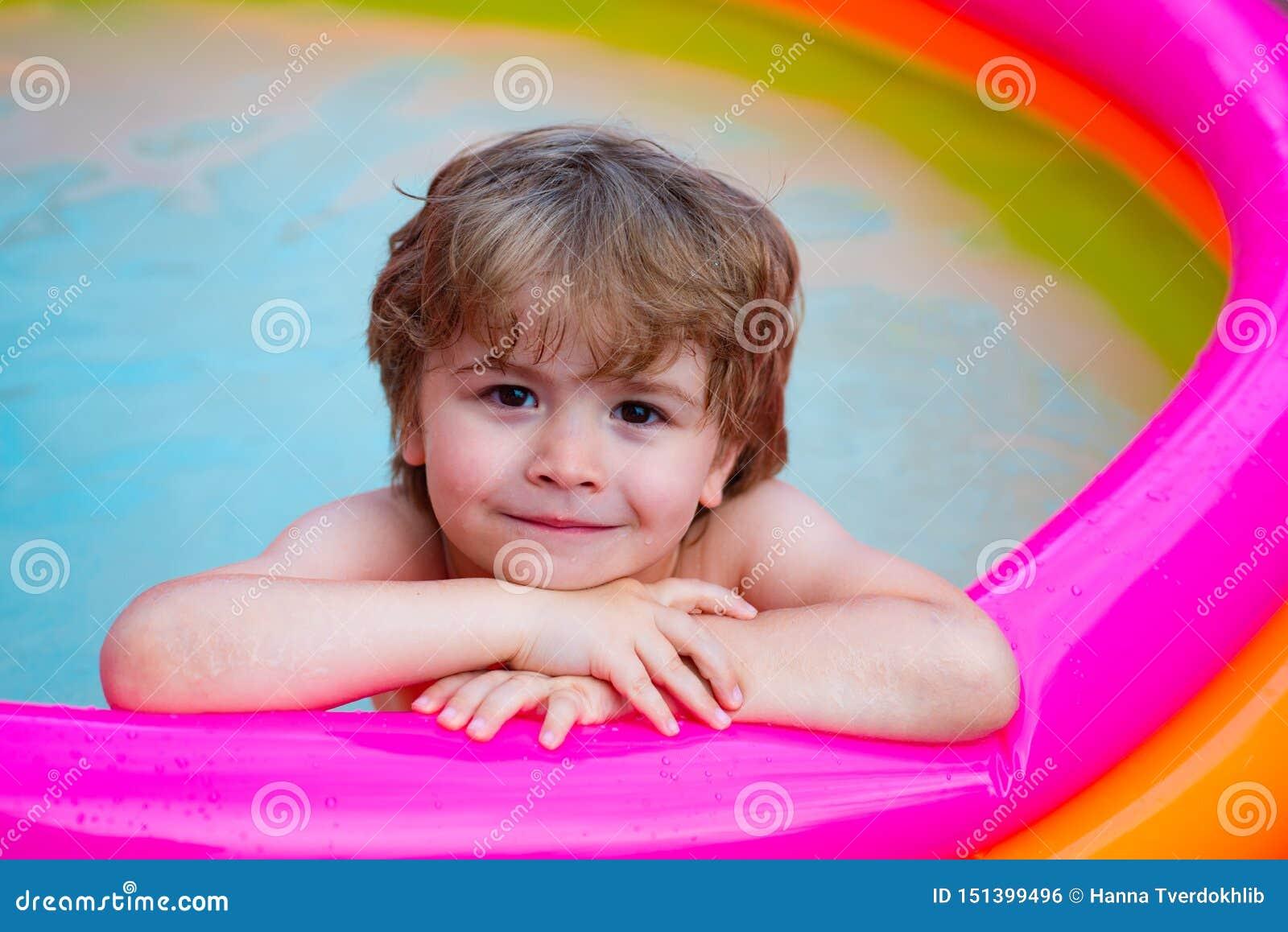 Релаксация лета в бассейне Ребенок лежит и ослабляет в домашнем бассейне с улыбкой Каникулы остатков лета Милый младенец