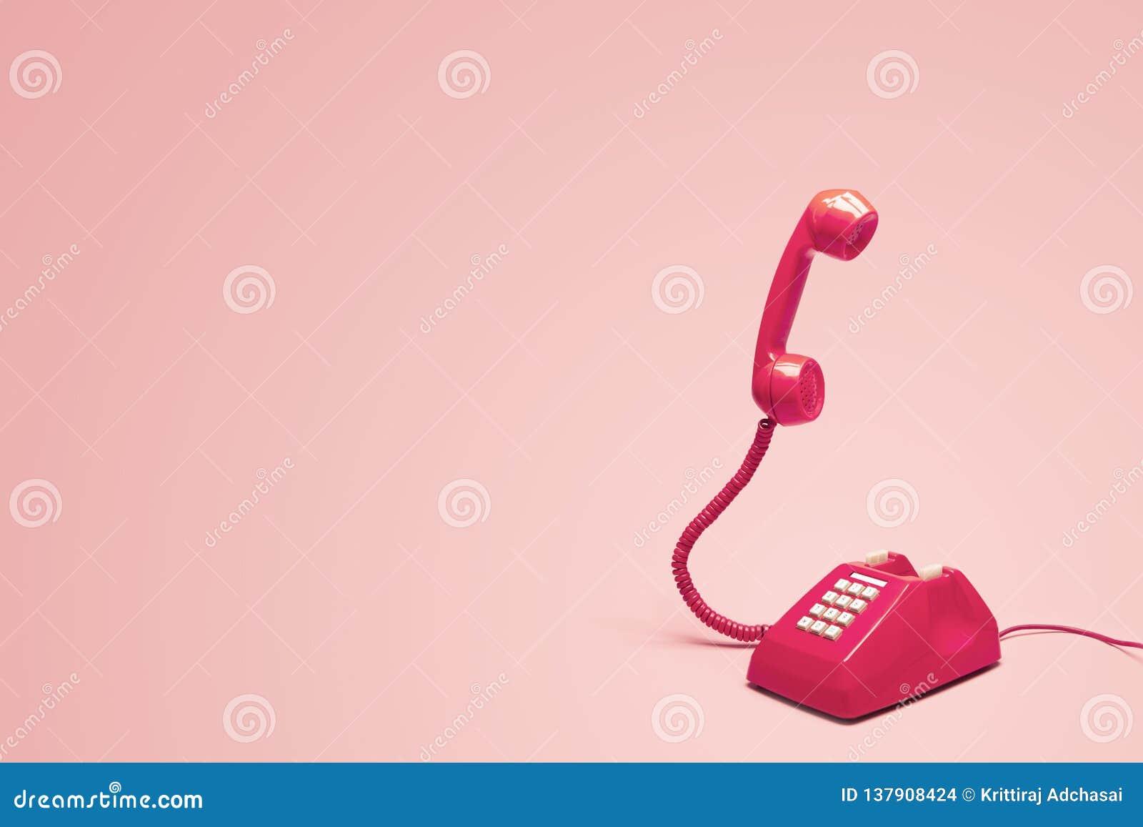 Ретро розовый телефон на ретро розовой предпосылке