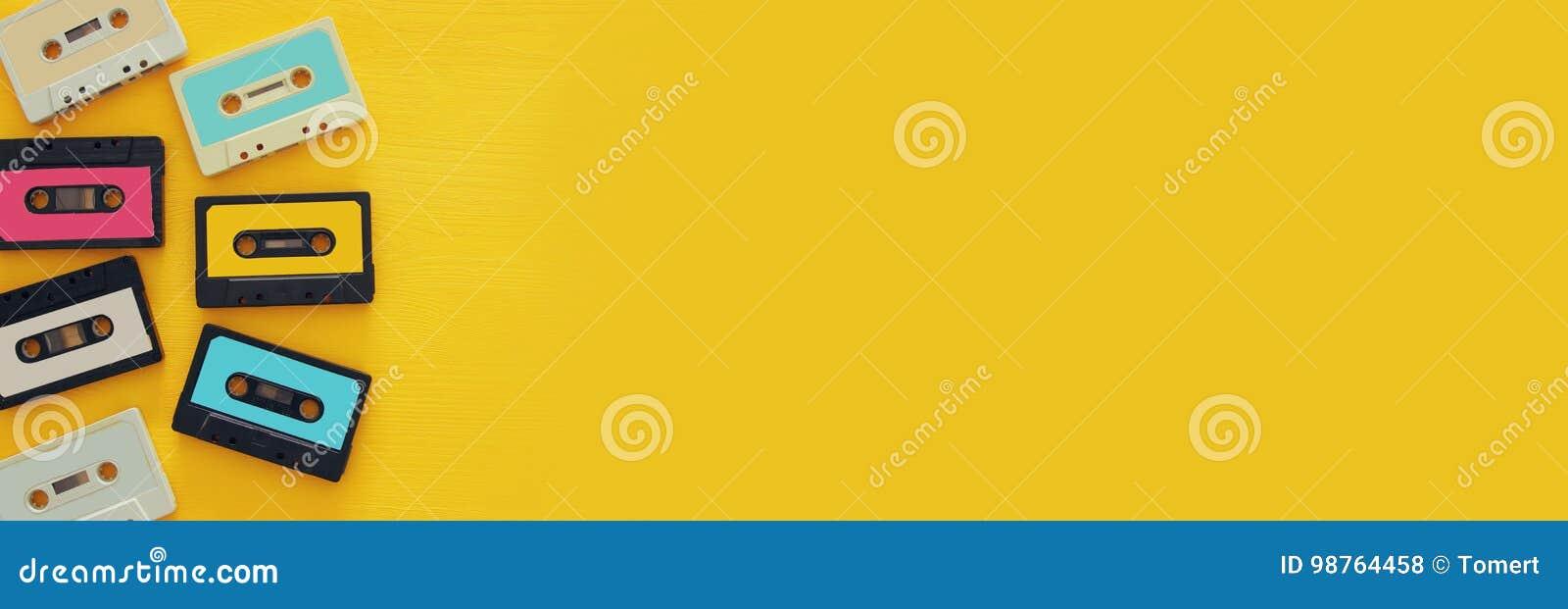 Ретро собрание кассеты над желтым деревянным столом Взгляд сверху скопируйте космос