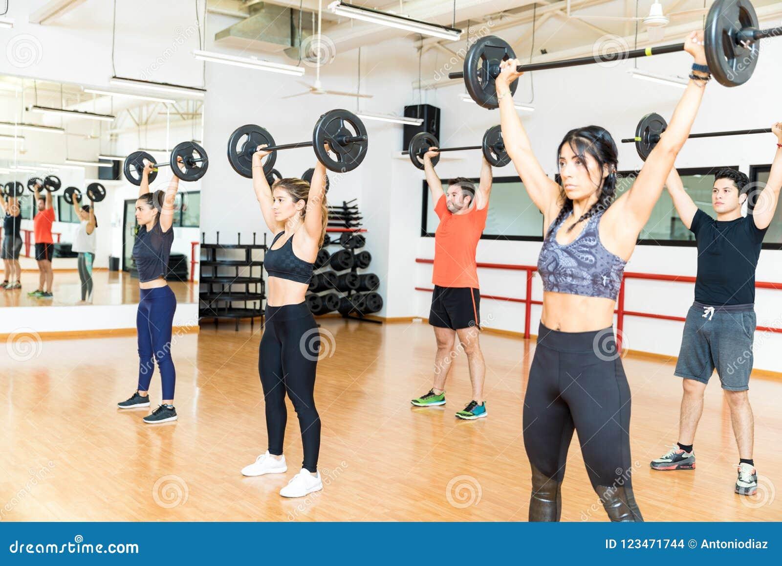 Решительно люди и женщины поднимая штанги в спортзале