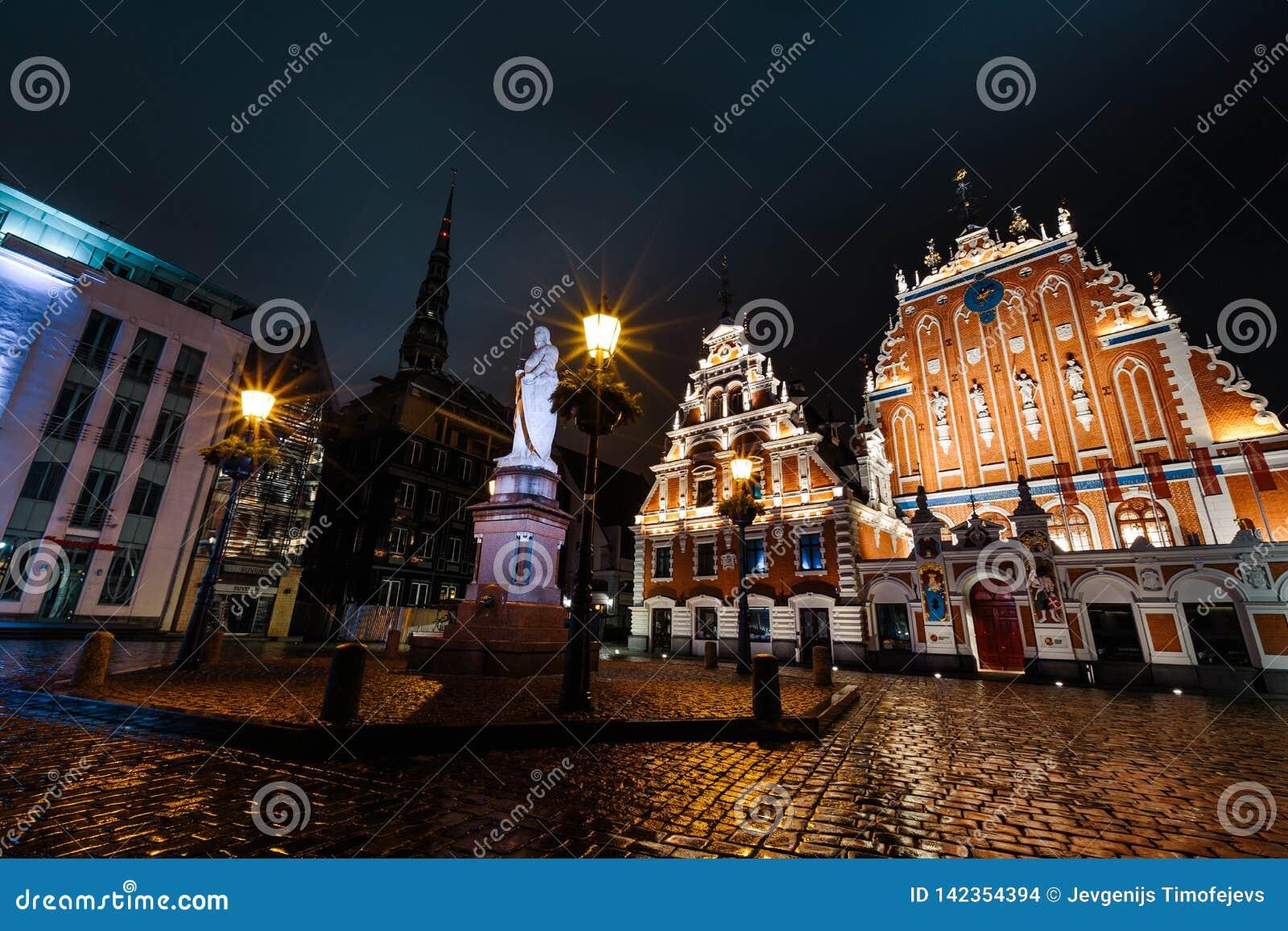 РИГА, ЛАТВИЯ - 17-ОЕ МАРТА 2019: Профессиональная съемка долгой выдержки дождливой ночью смотря на дом угорь, статую