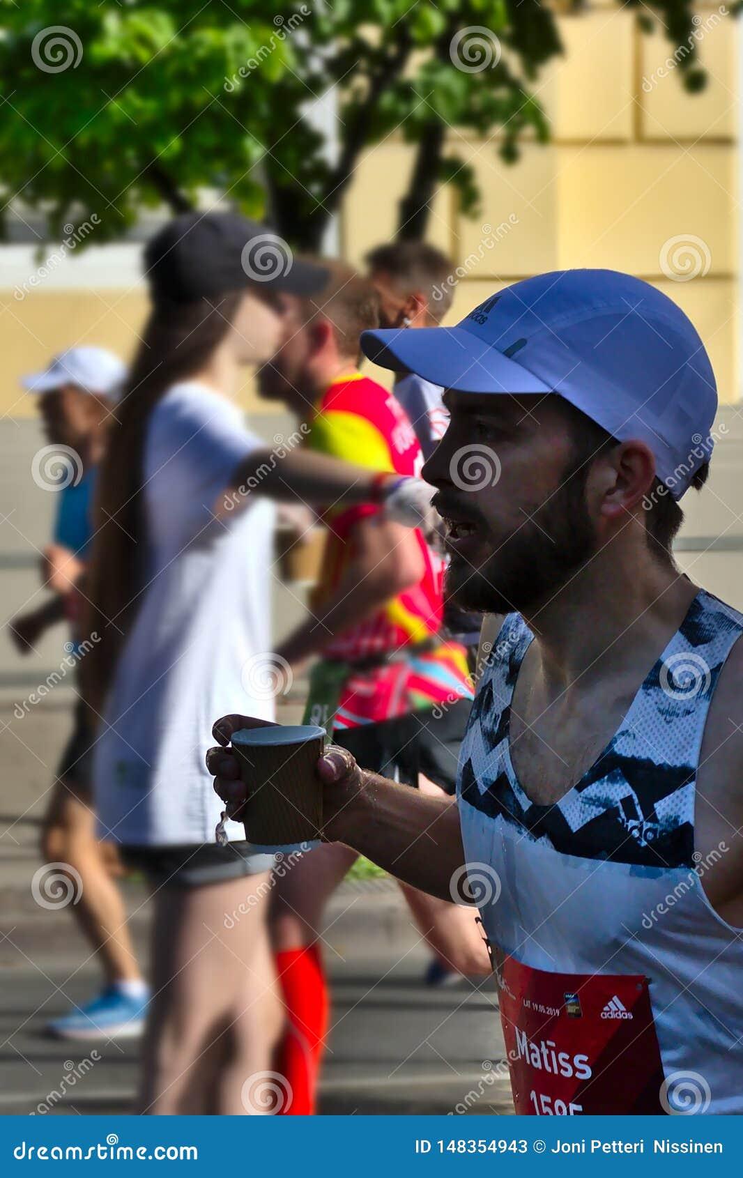 Рига, Латвия - 19-ое мая 2019: Бородатый человек бежать с чашкой в его руке