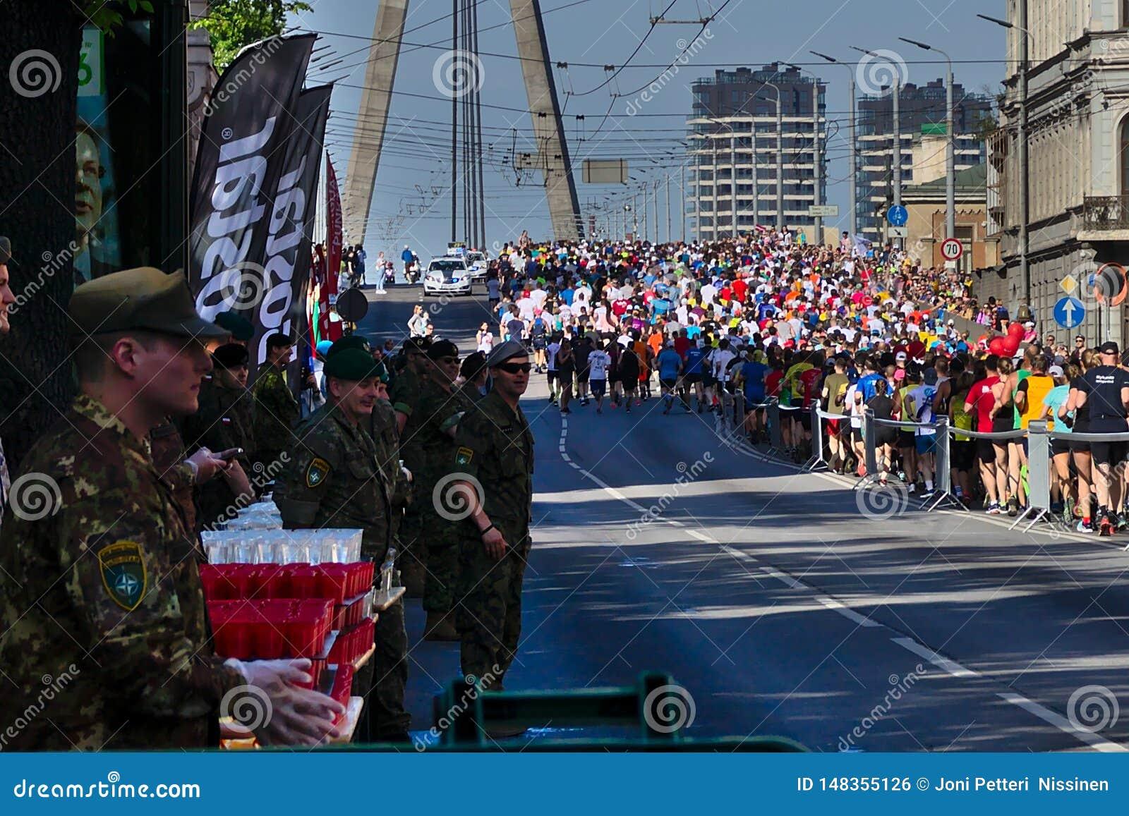 Рига, Латвия - 19-ое мая 2019: Военные волонтеры ждать марафонцы