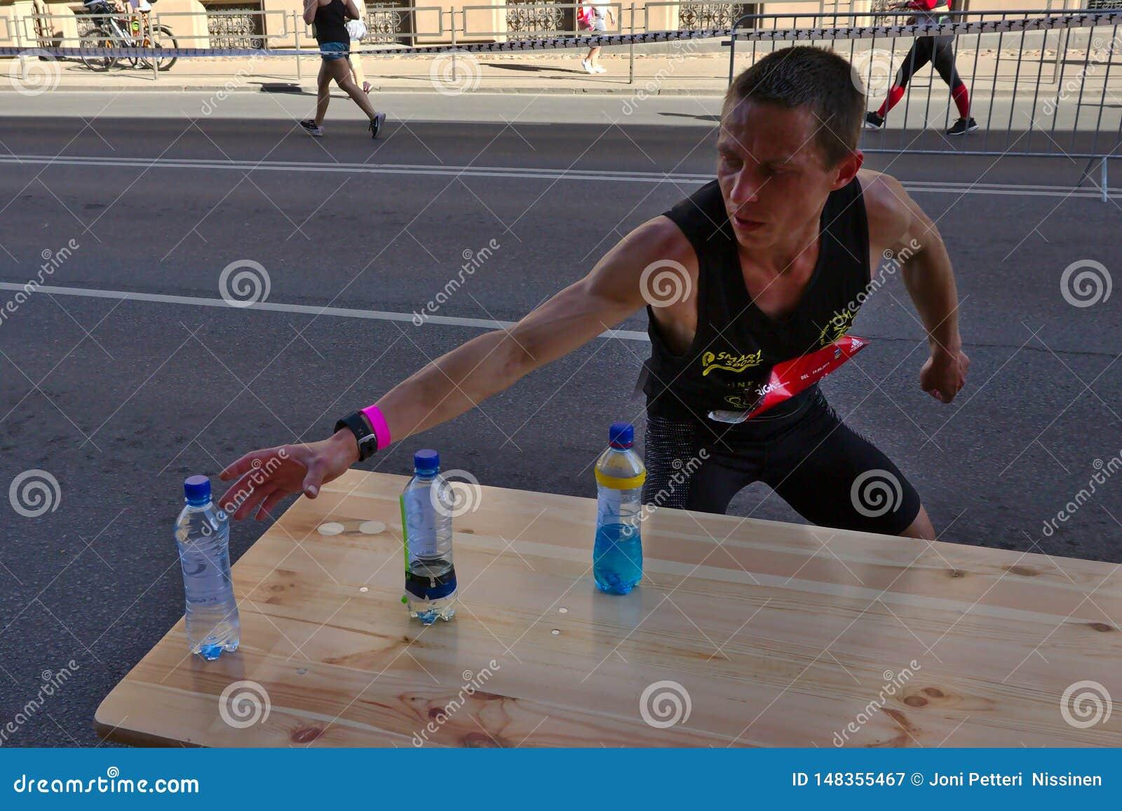 Рига, Латвия - 19-ое мая 2019: Кавказский бегун Томми элиты ища спорт выпивает