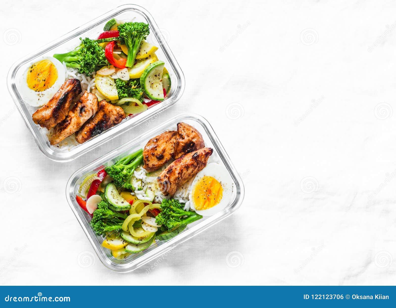 Рис, потушенные овощи, яичко, цыпленок teriyaki - здоровая сбалансированная коробка для завтрака на светлой предпосылке, взгляд с
