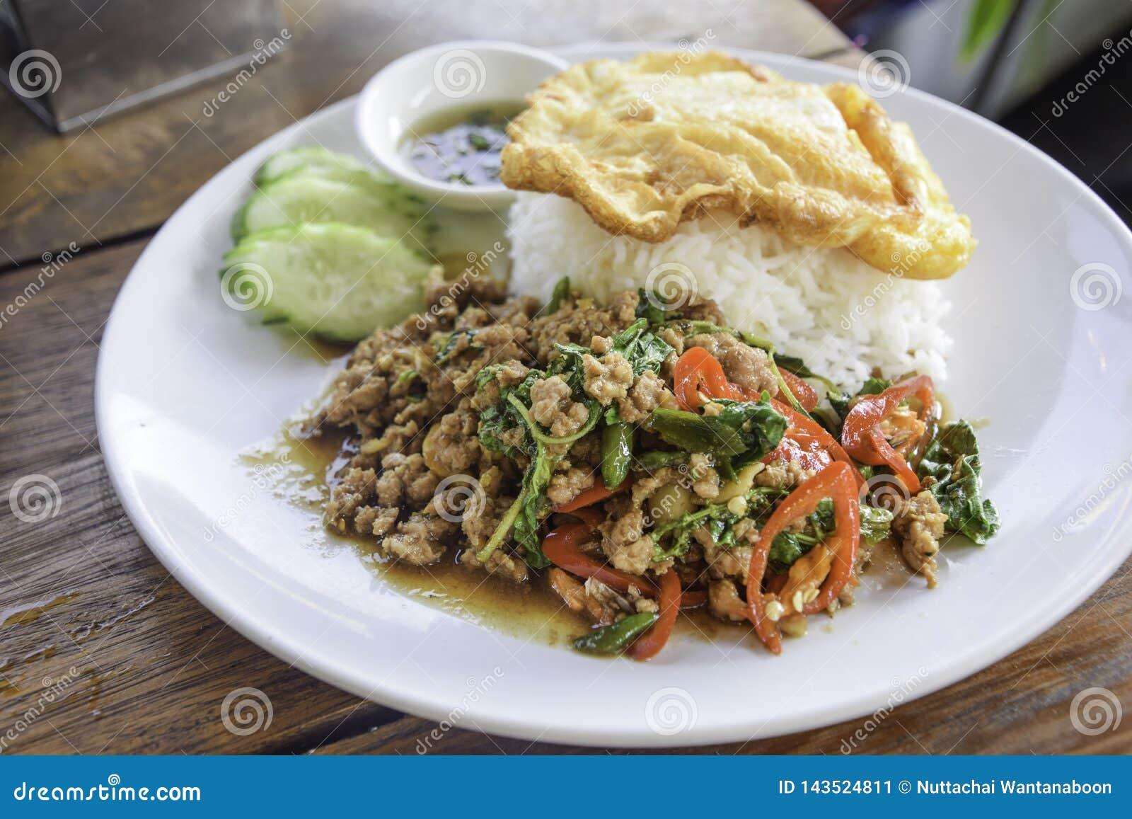 Рис с Шевелить-зажаренной свининой с листьями базилика на белом блюде