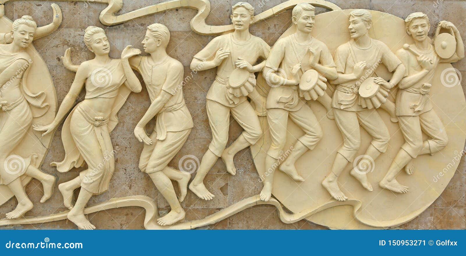 Родной камень тайских людей культуры танцуя высекая на стене виска