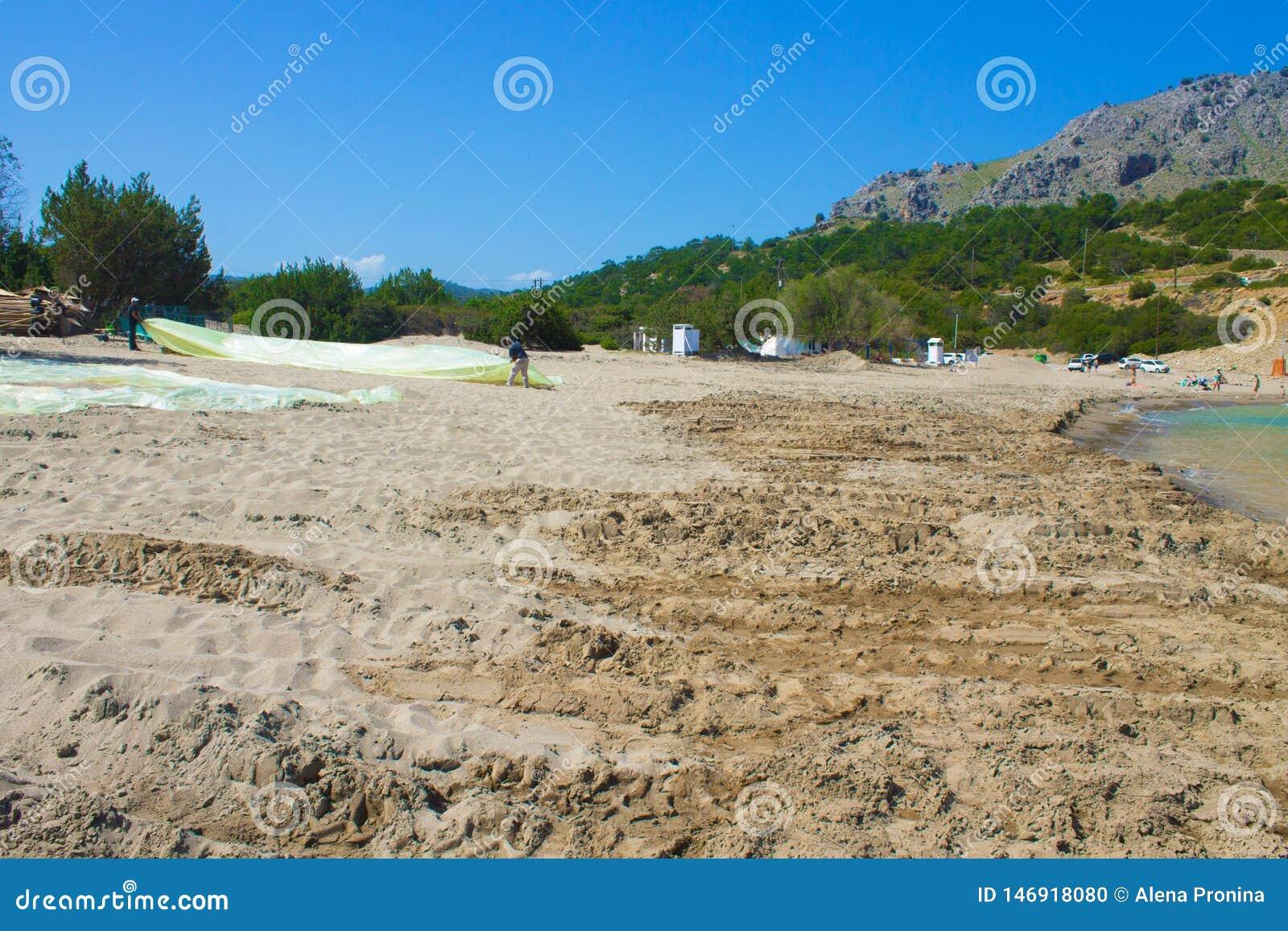 Родос, Греция, апрель 2019 2 люд складывают полиэтилен на пляже, подготавливают пляж в заливе на сезон