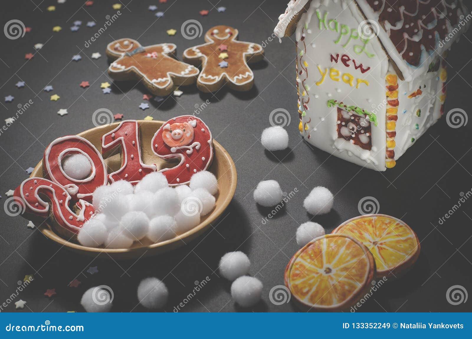 Рождественская открытка: на деревянной плите печенья красного имбиря в форме 2019 и белые круглые снежинки