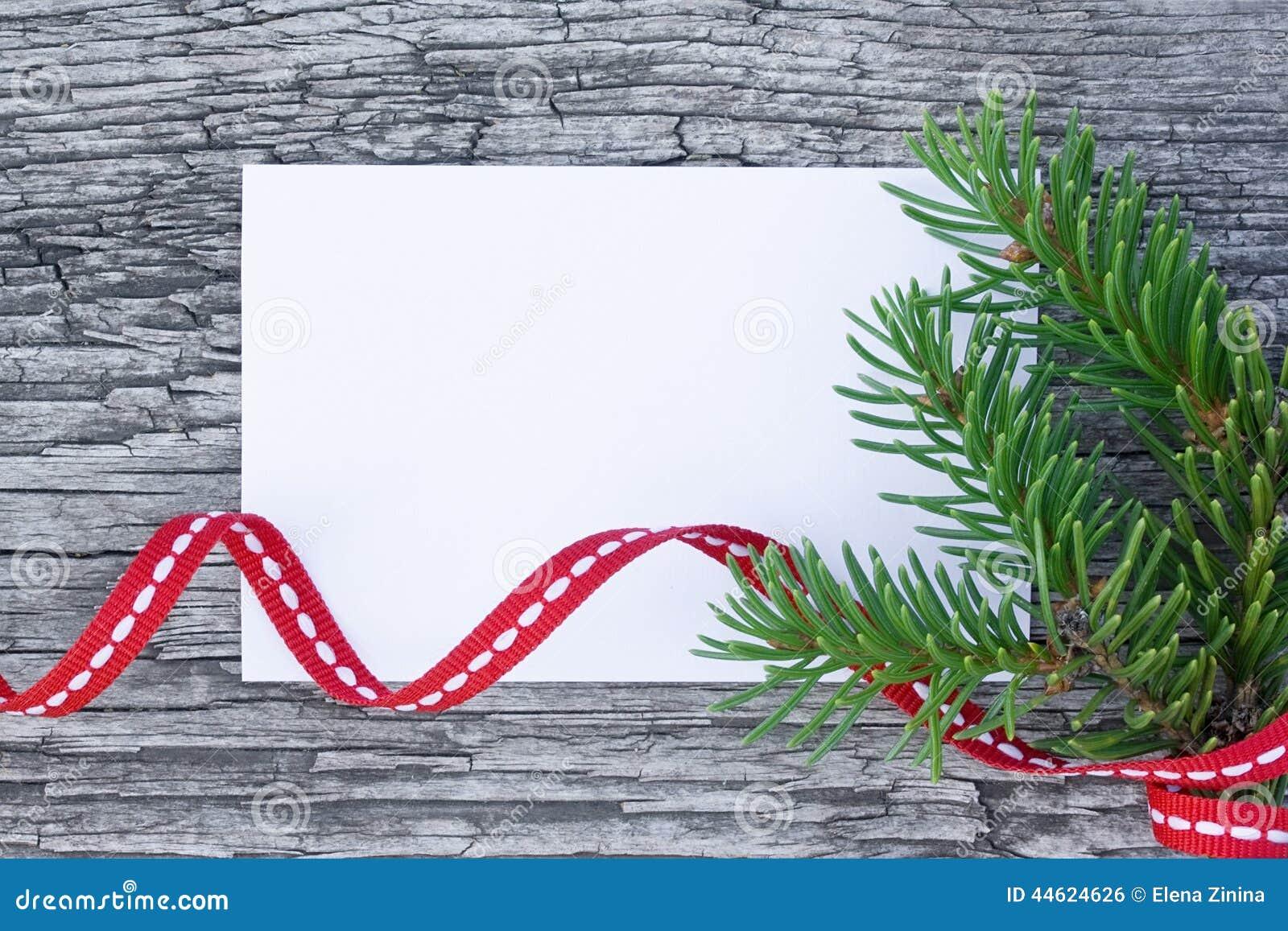 Рождественская открытка: пустая бумага с елью разветвляет на деревянной предпосылке