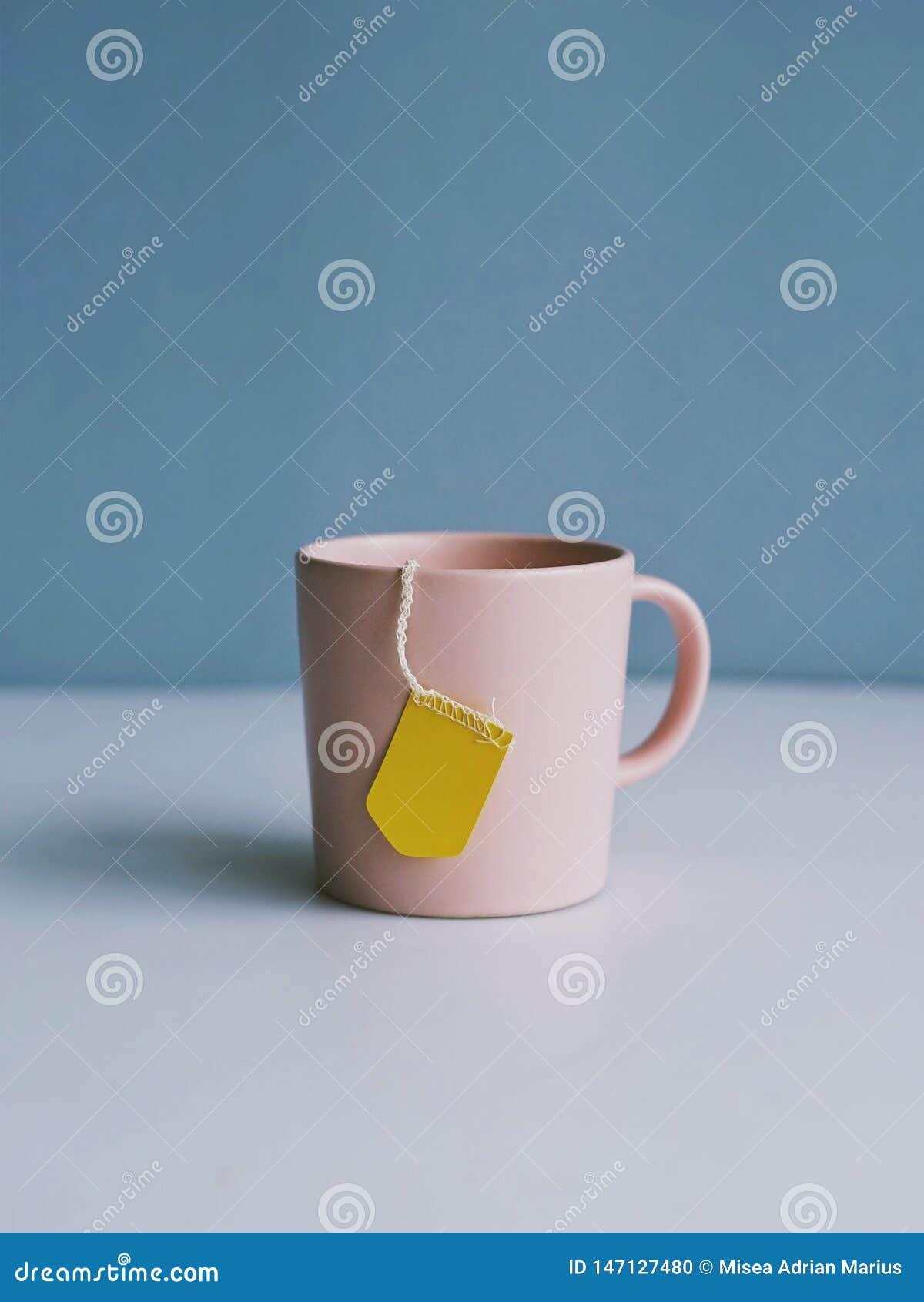 Розовая чашка чаю на светлом - голубая предпосылка
