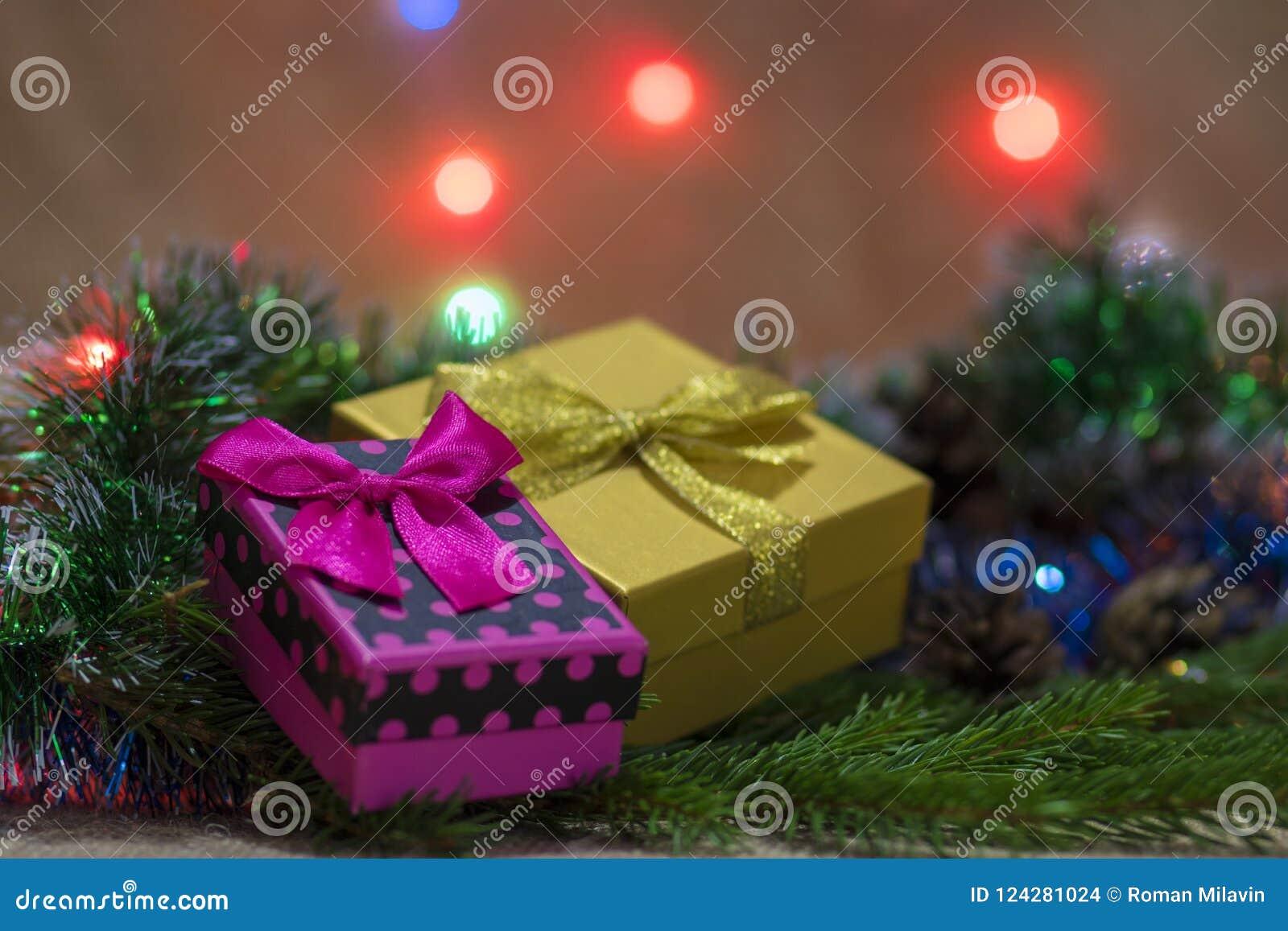 Розовые и оранжевые коробки с подарками рождества с смычками и bokeh на заднем плане