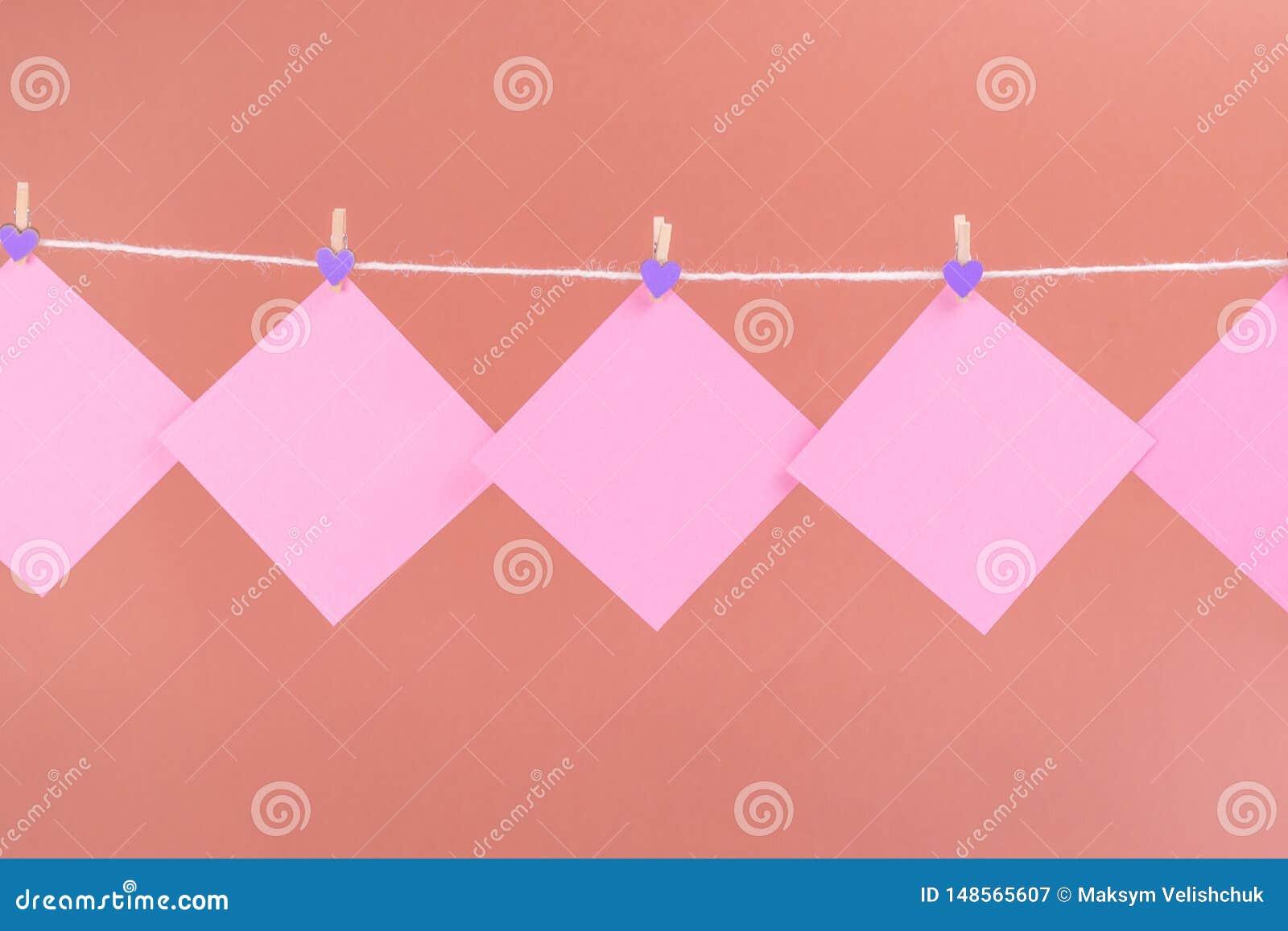 Розовые стикеры на веревке для белья с зажимками для белья изолированными на коричневой предпосылке
