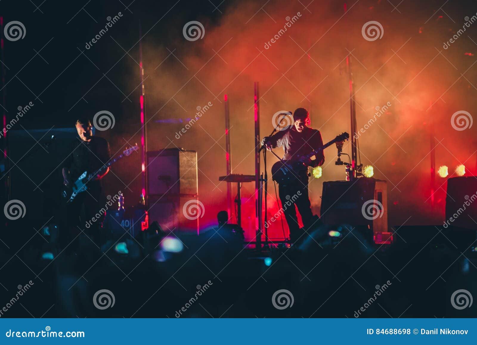 Рок-группа выполняет на этапе Гитарист играет solo Силуэт гитариста в действии на этапе перед толпой концерта