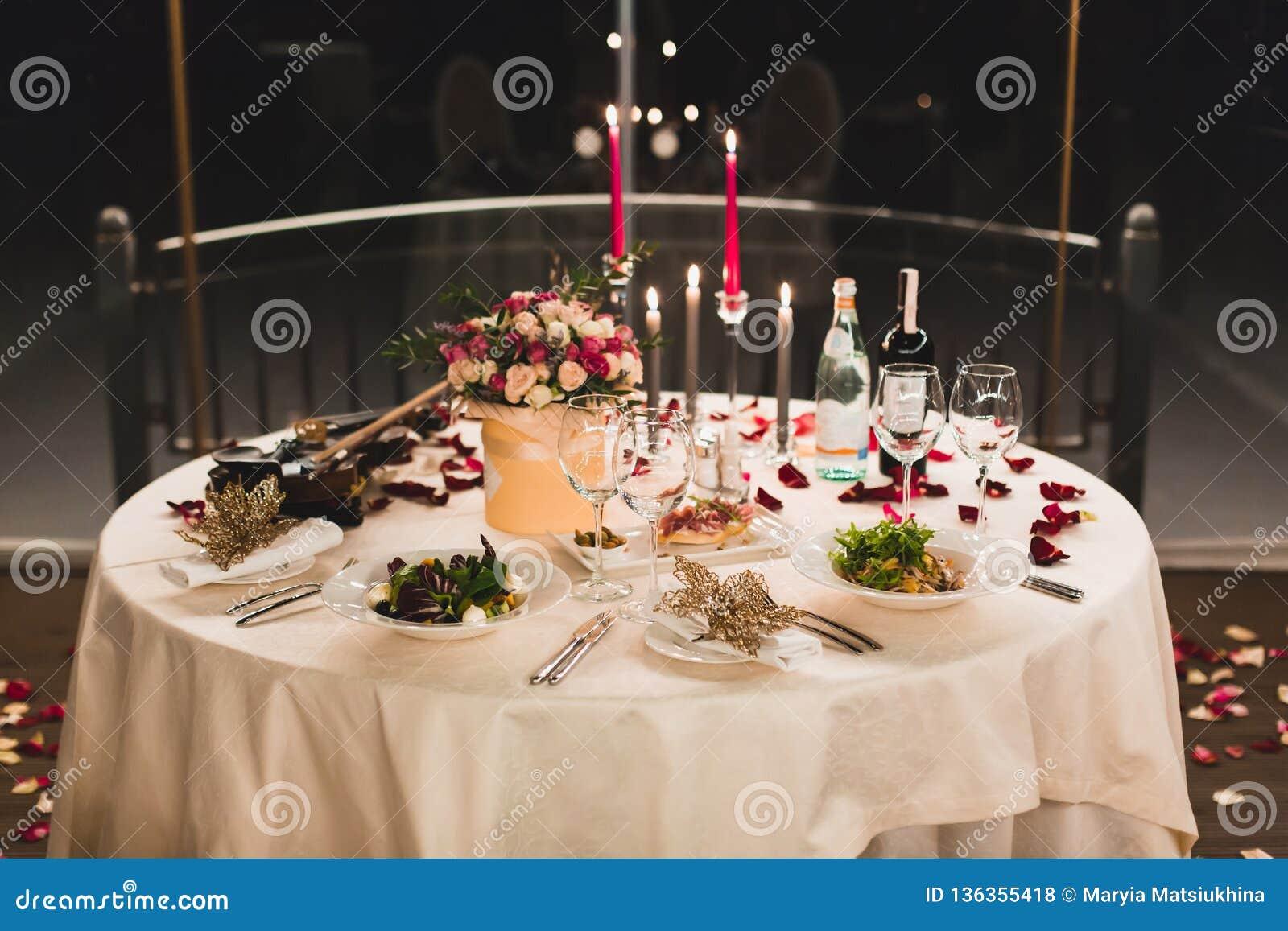 Романтичная сервировка стола с вином, красивыми цветками в коробке, пустыми стеклами, лепестками розы и свечами