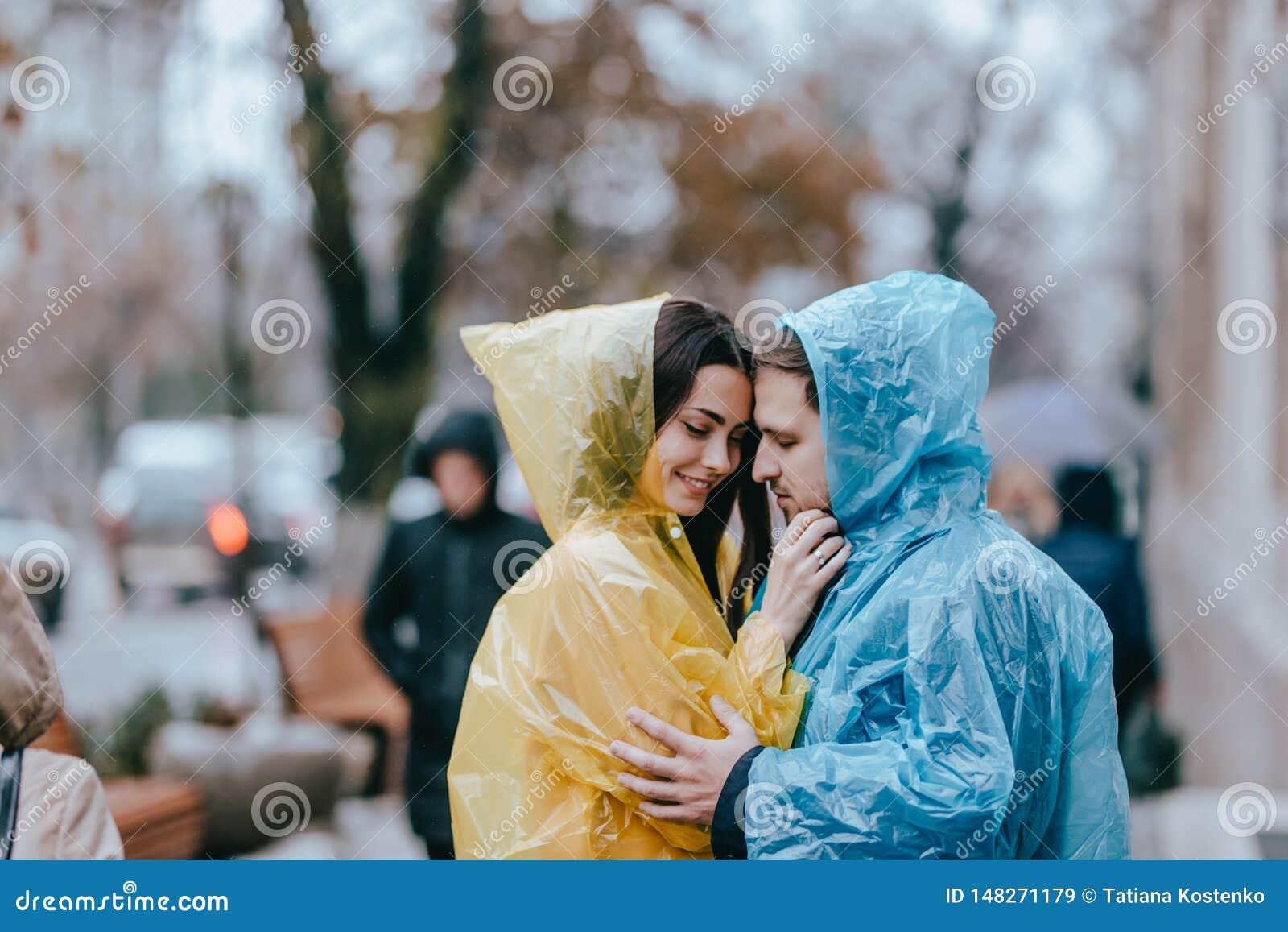 Романтичные любящие пары, парень и его девушка в плащах стоят лицом к лицу на улице в дожде