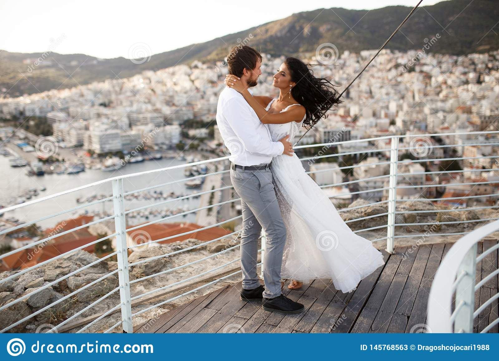 Романтичный взгляд счастливых пар в белых одеждах Красивый ландшафт солнца над городом во время захода солнца
