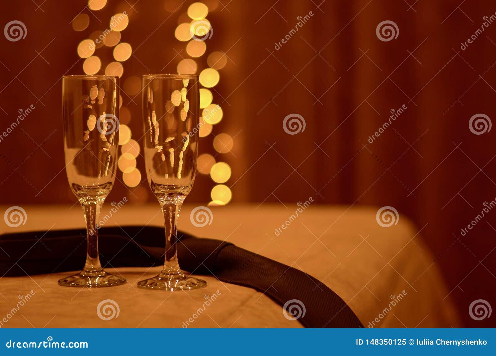 2 романтичных стекла на краю кровати в свете теплых светов, рядом со связью человека