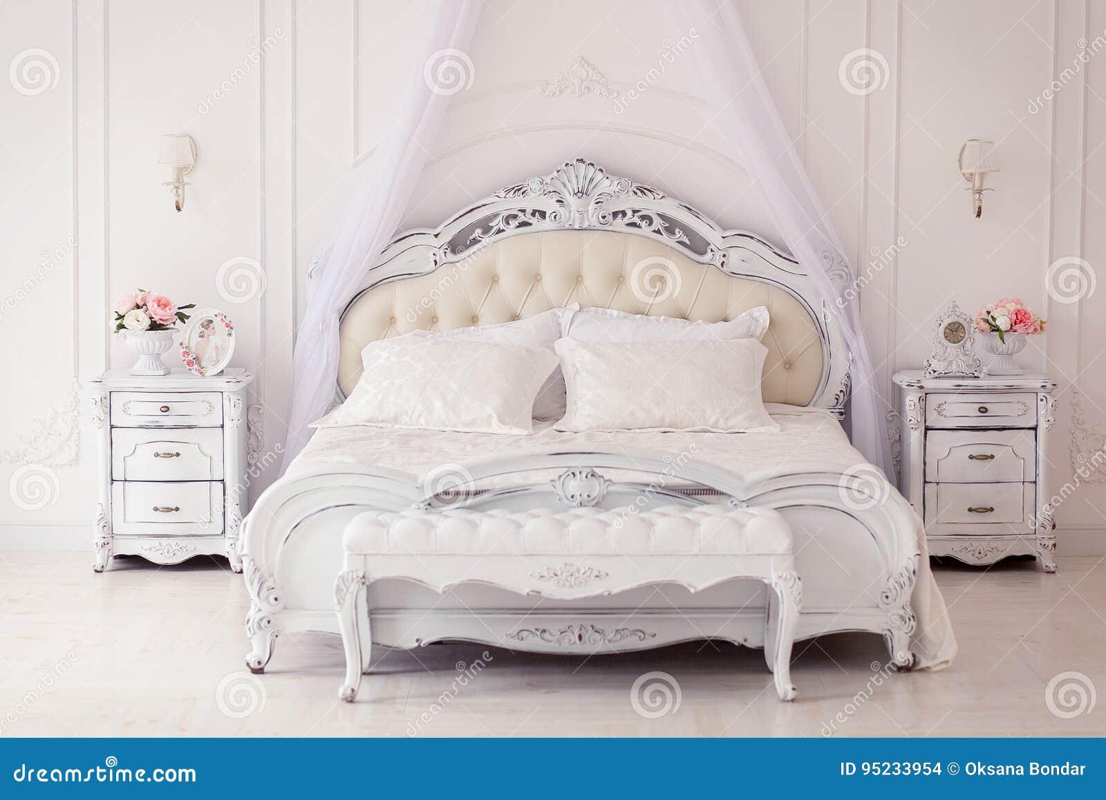 роскошная спальня в светлых цветах с золотыми деталями мебели