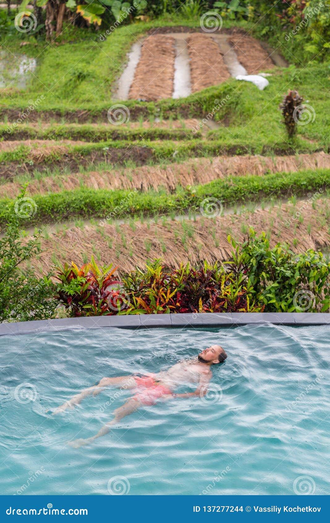 Роскошный курорт Человек ослабляя в воде бассейна безграничности Красивая счастливая здоровая мужская модель наслаждаясь перемеще
