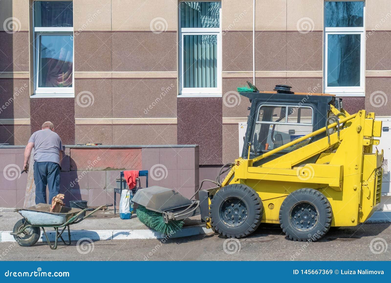 Россия, Казань - 12-ое апреля 2019: Пожилой человек кладет плитки на стену снаружи