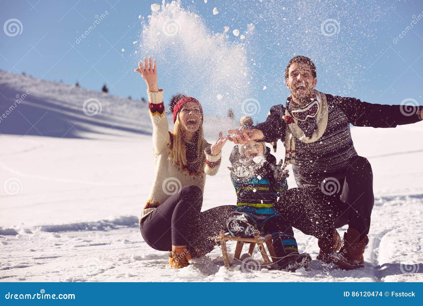 Родительство, мода, сезон и концепция людей - счастливая семья при ребенок на скелетоне идя в зиму outdoors