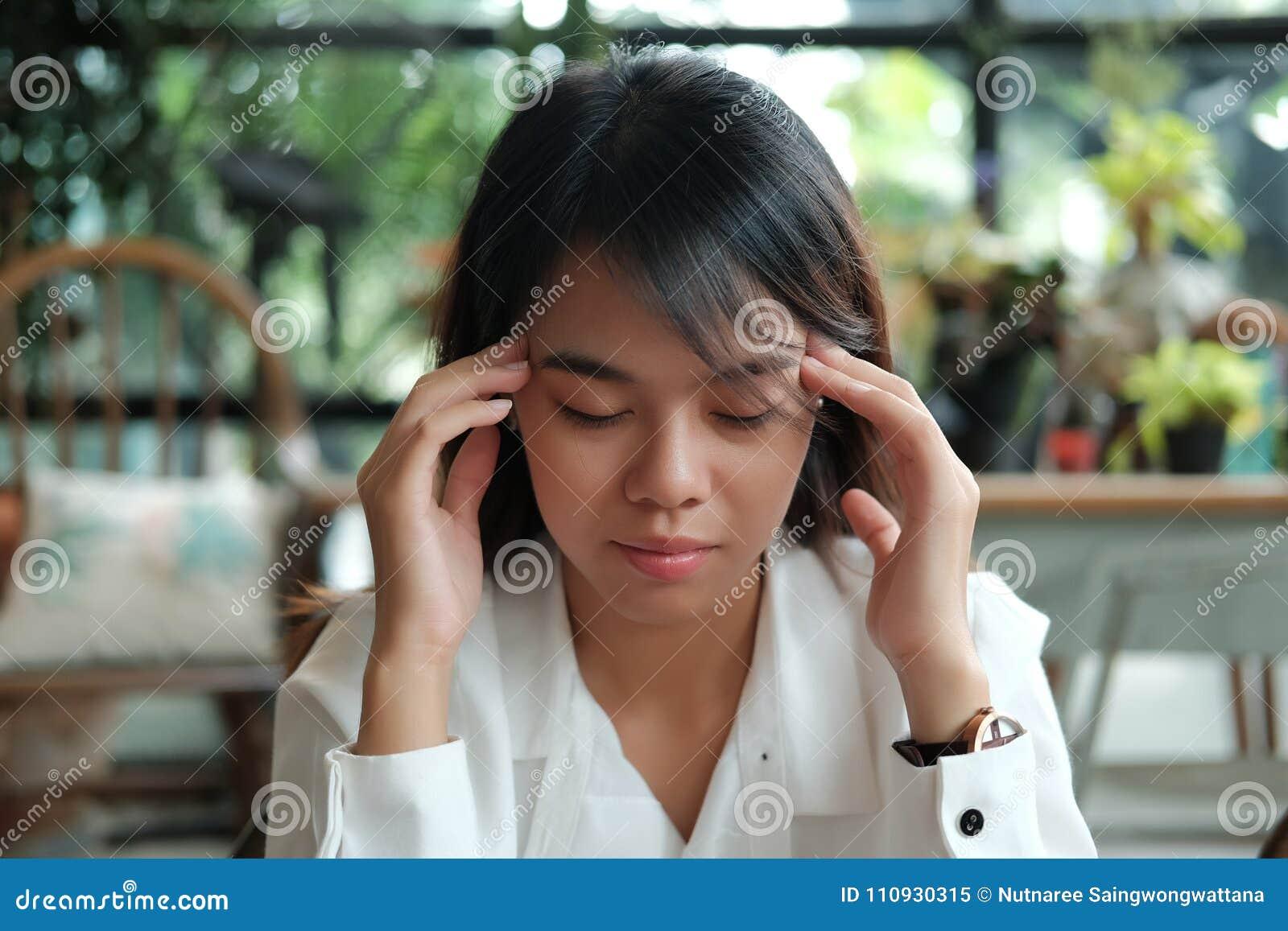 Рубашка молодой женщины студента нося белая с головной болью и holdin