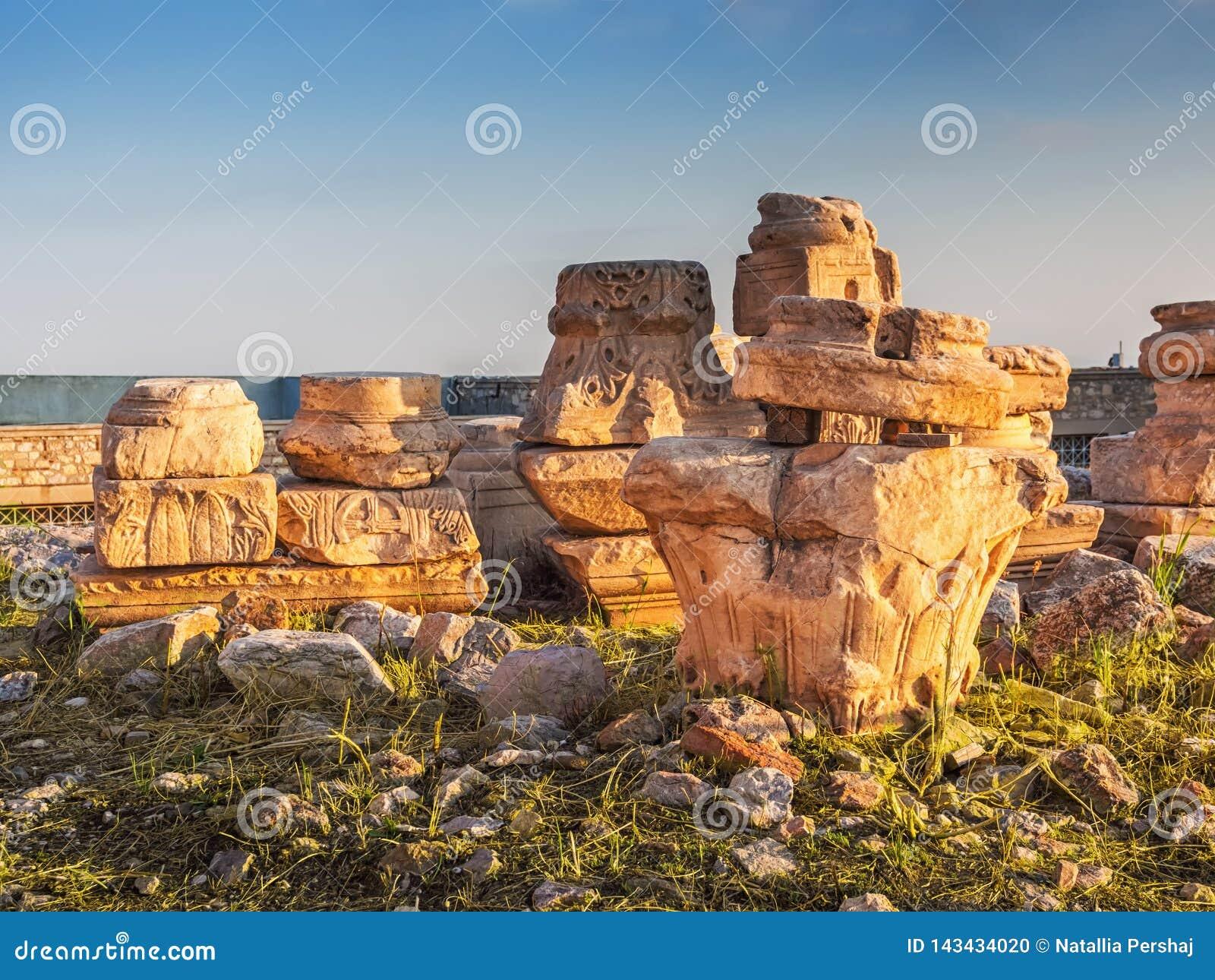 Руины и части старых столбцов, capitels и оснований с греческими и христианскими символами в свете захода солнца