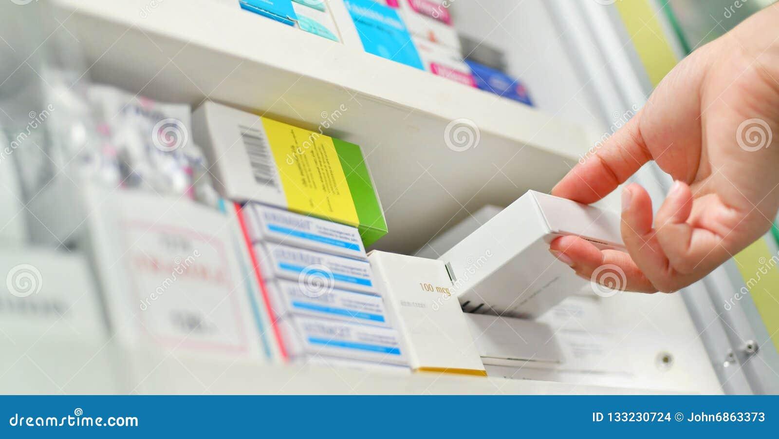 рука аптекаря держа коробку медицины в аптеке