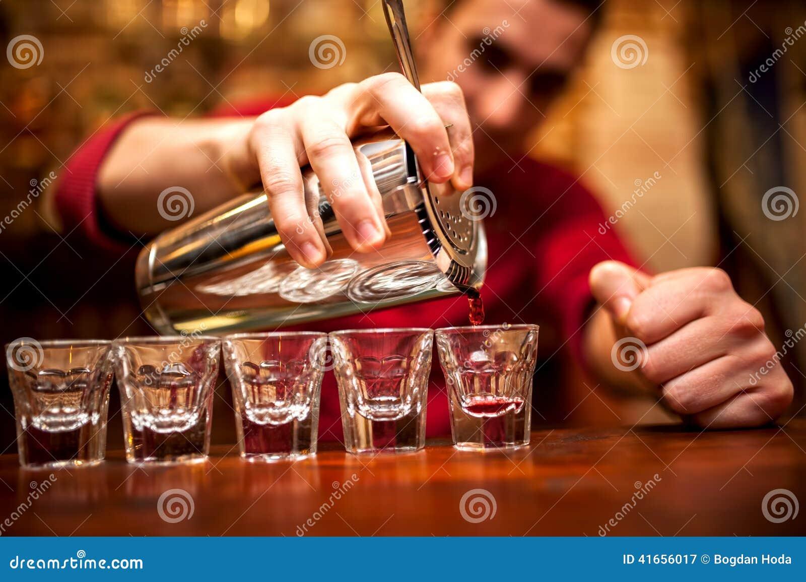 Рука бармена с напитком смесителя встряхивания лить в стекла