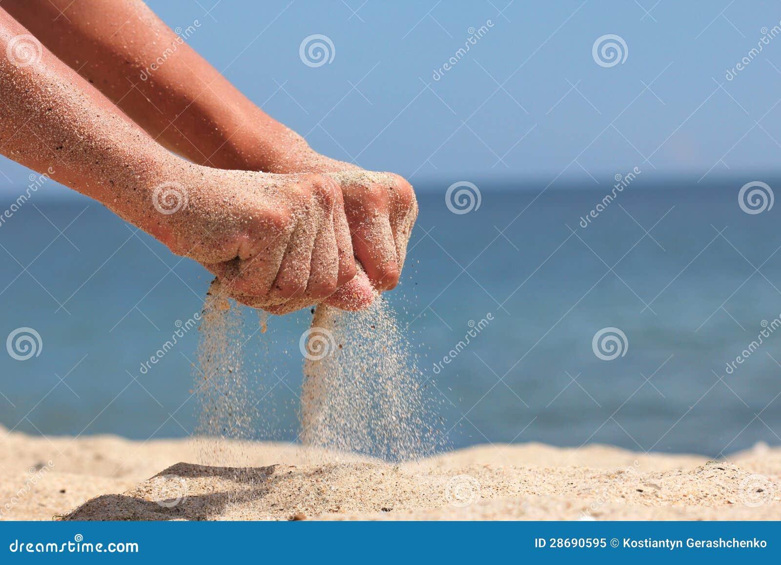 Рука бросает песок