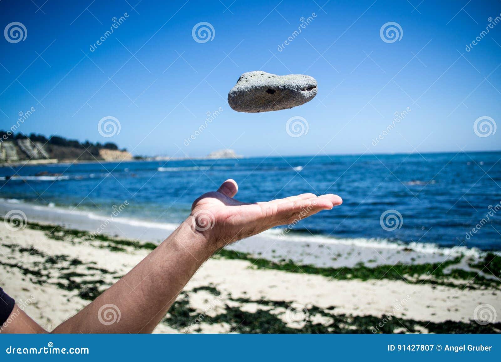 Рука бросая камень